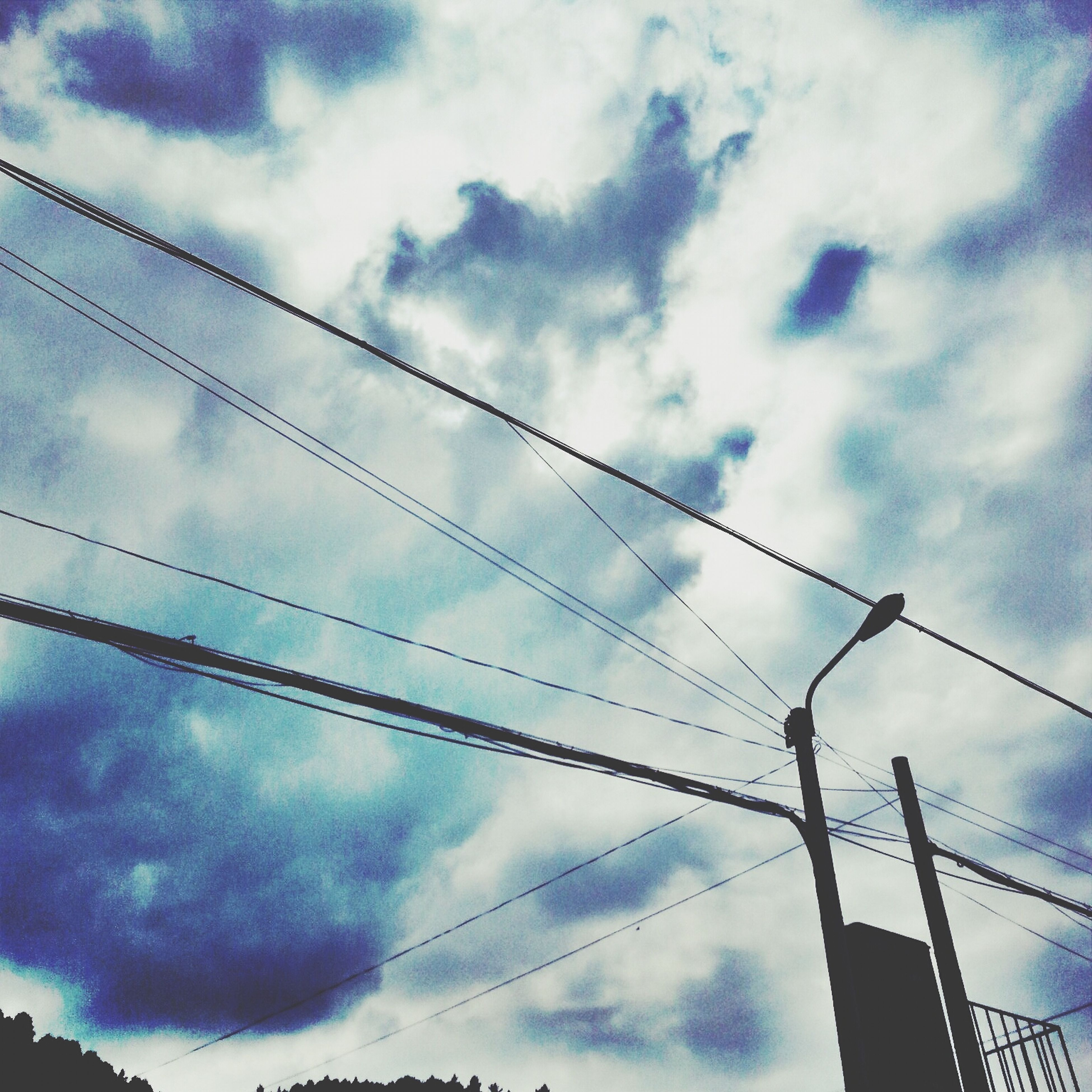 low angle view, sky, power line, connection, cloud - sky, cable, power supply, electricity pylon, cloudy, electricity, cloud, silhouette, fuel and power generation, technology, power cable, blue, built structure, outdoors, no people, weather