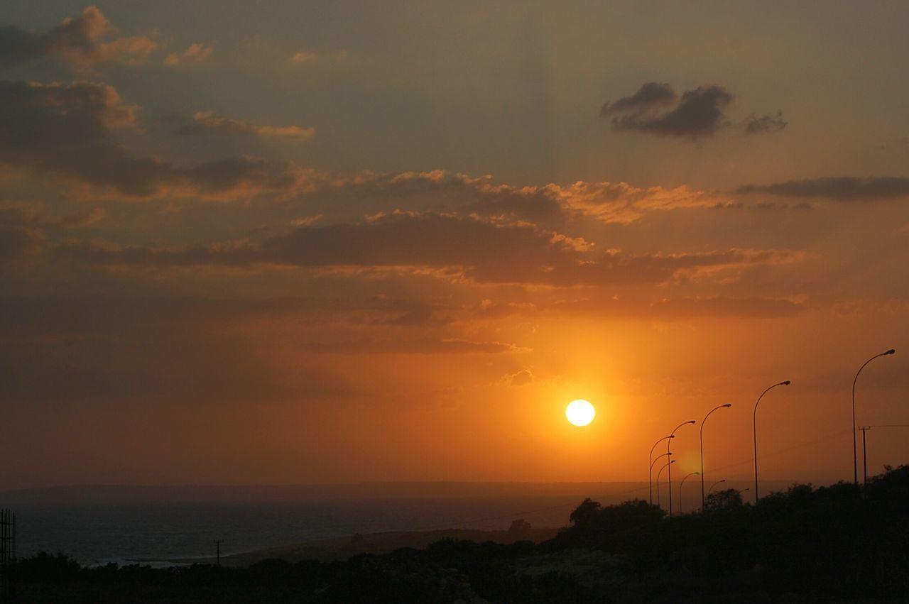 Scenic View Of Landscape Against Orange Sunset Sky