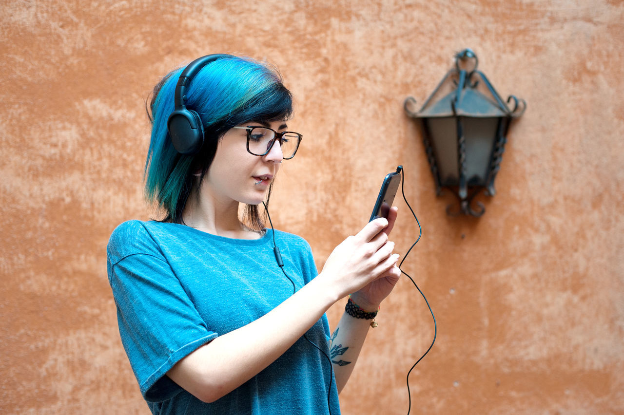Pretty teen hypster style woman listening music with smart phone and headphones Alternative Blue Casual Clothing Cute Day Eyeglasses  Girl Headphones Hypster Listening Music One Person Portable Information Device Pretty Smart Phone Teen Teenager Using Phone Woman Young Youth Culture