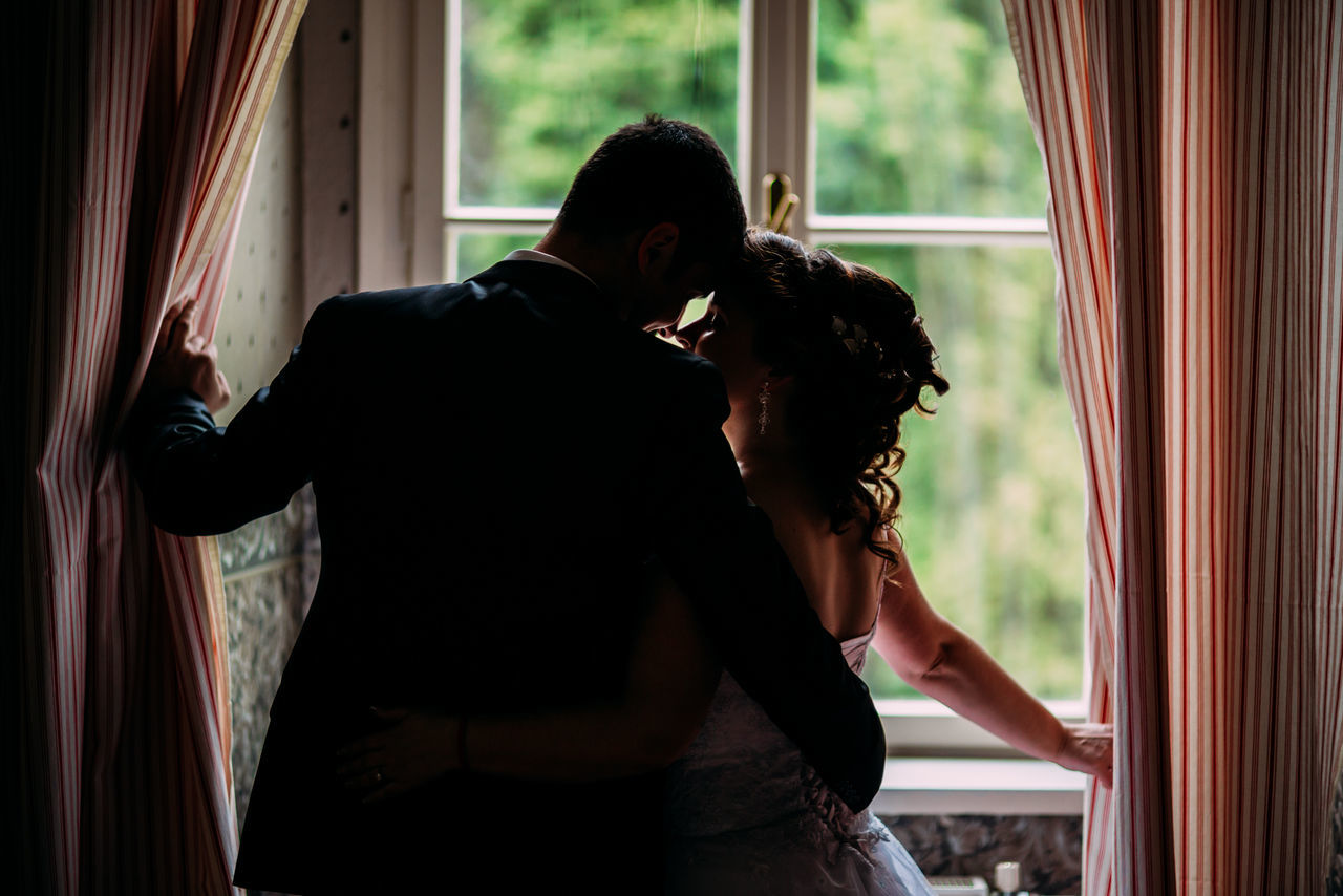 curtain, two people, window, indoors, love, togetherness, heterosexual couple, home interior, standing, men, real people, young women, drapes, bonding, lifestyles, young adult, day, beautiful woman, bride, adult, people