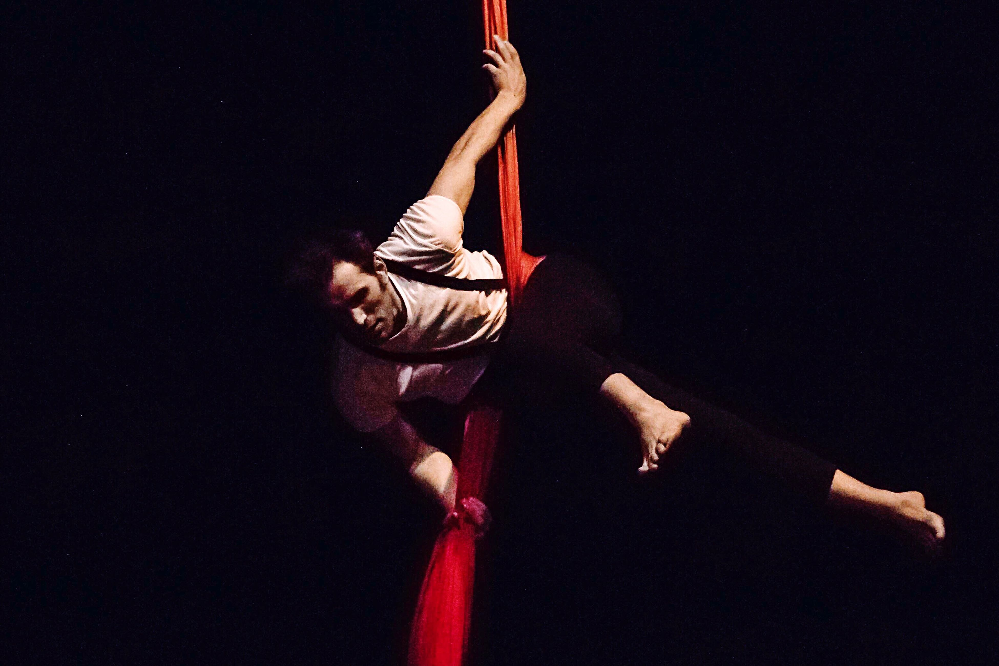 strength, full length, skill, balance, upside down, real people, performance, handstand, one person, flexibility, lifestyles, acrobat, exercising, concentration, black background, leisure activity, studio shot, men, young adult, acrobatic activity, indoors, day, people