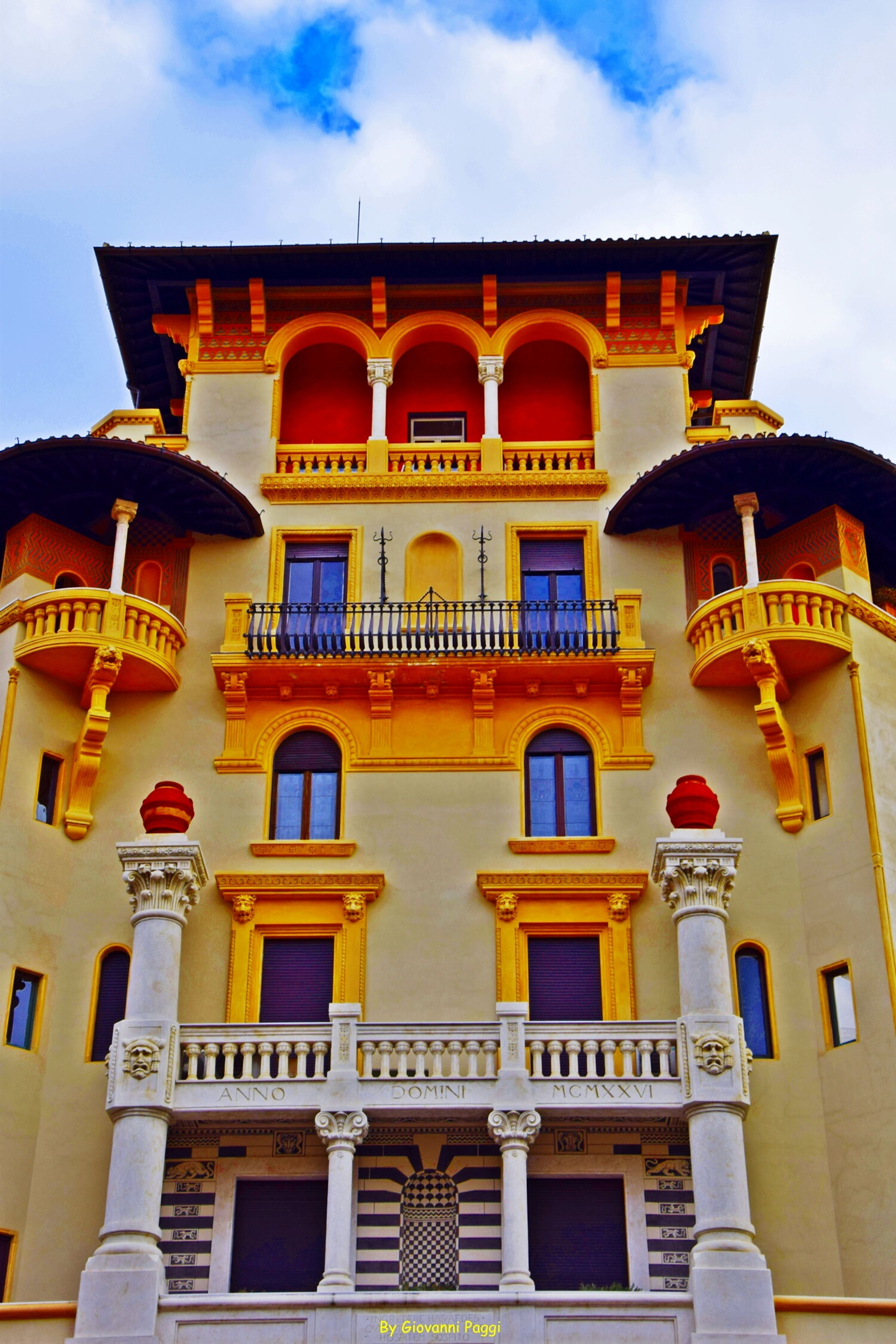 architecture, building exterior, built structure, low angle view, window, sky, building, arch, facade, balcony, residential building, yellow, residential structure, cloud - sky, outdoors, day, cloud, no people, sunlight, city
