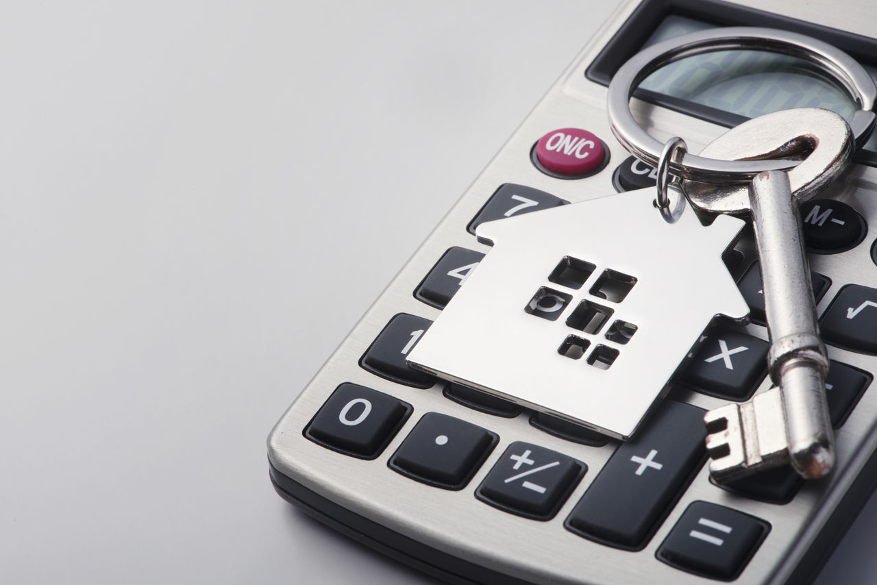 Home shape key chain and calculator Budget Business House Shape Planning Calculation Calculator Close Up Concept Financing House House Keys Housing Loan Interest Investment Key Keychain Metal Mortgage Property Saving White Background