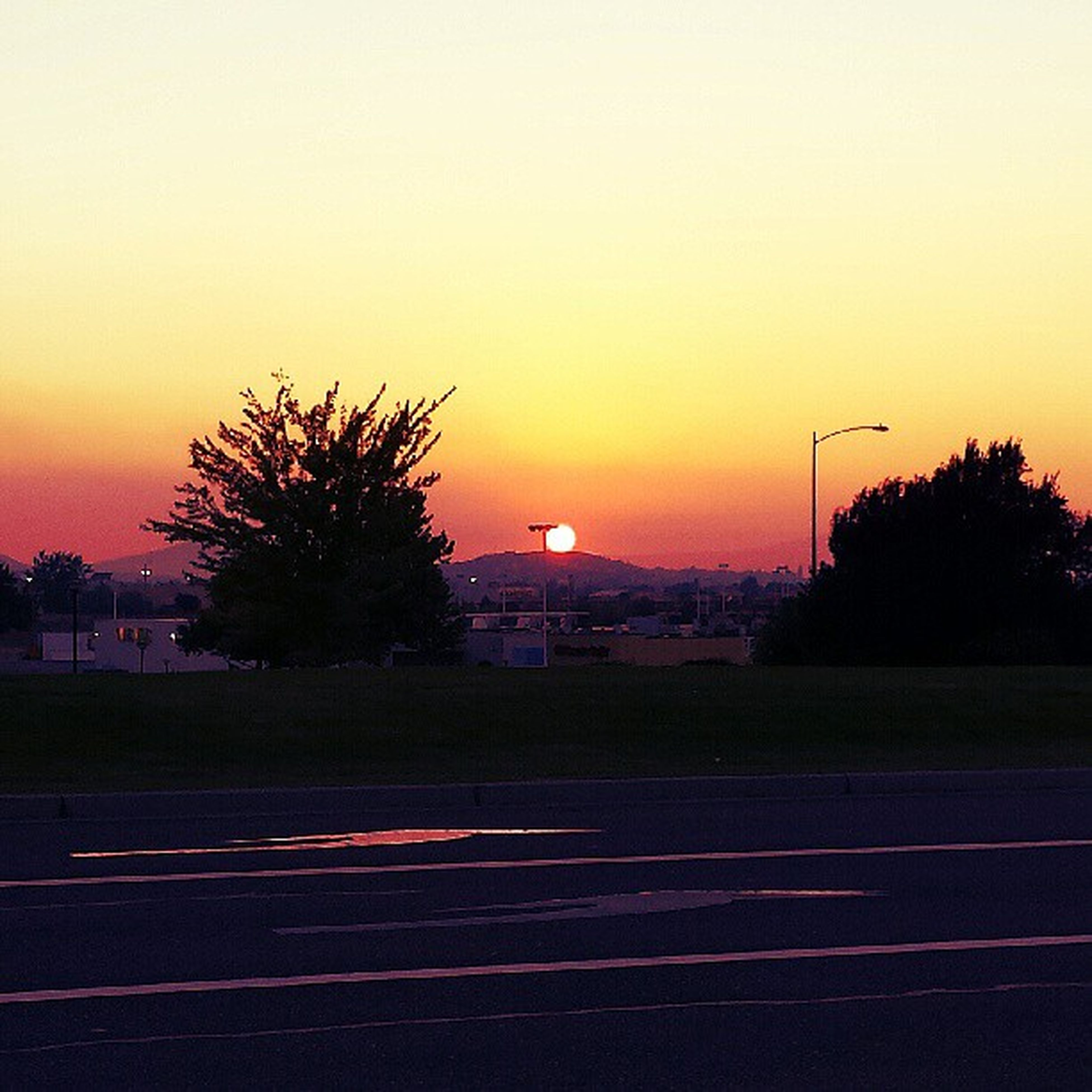 sunset, silhouette, orange color, tree, road, landscape, sky, transportation, clear sky, copy space, dusk, illuminated, scenics, tranquil scene, field, tranquility, beauty in nature, nature, street light, street