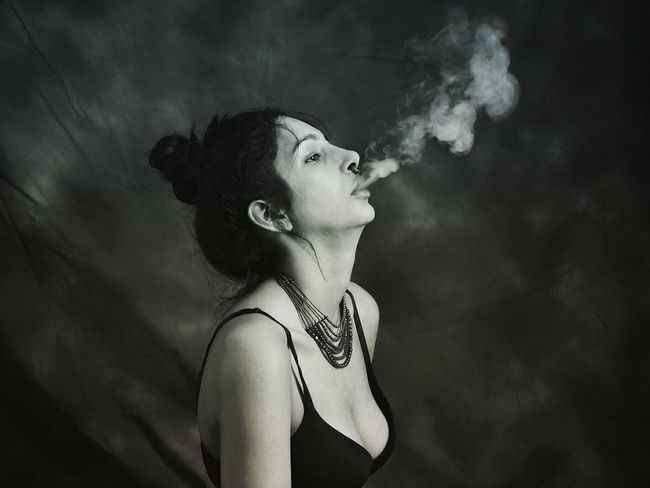 EyeEmNewHere Only Women One Woman Only Adults Only One Person Adult Profile View People One Young Woman Only Smoking - Activity Young Adult Side View Human Face Studio Shot Young Women Human Body Part Indoors  Black Background Close-up