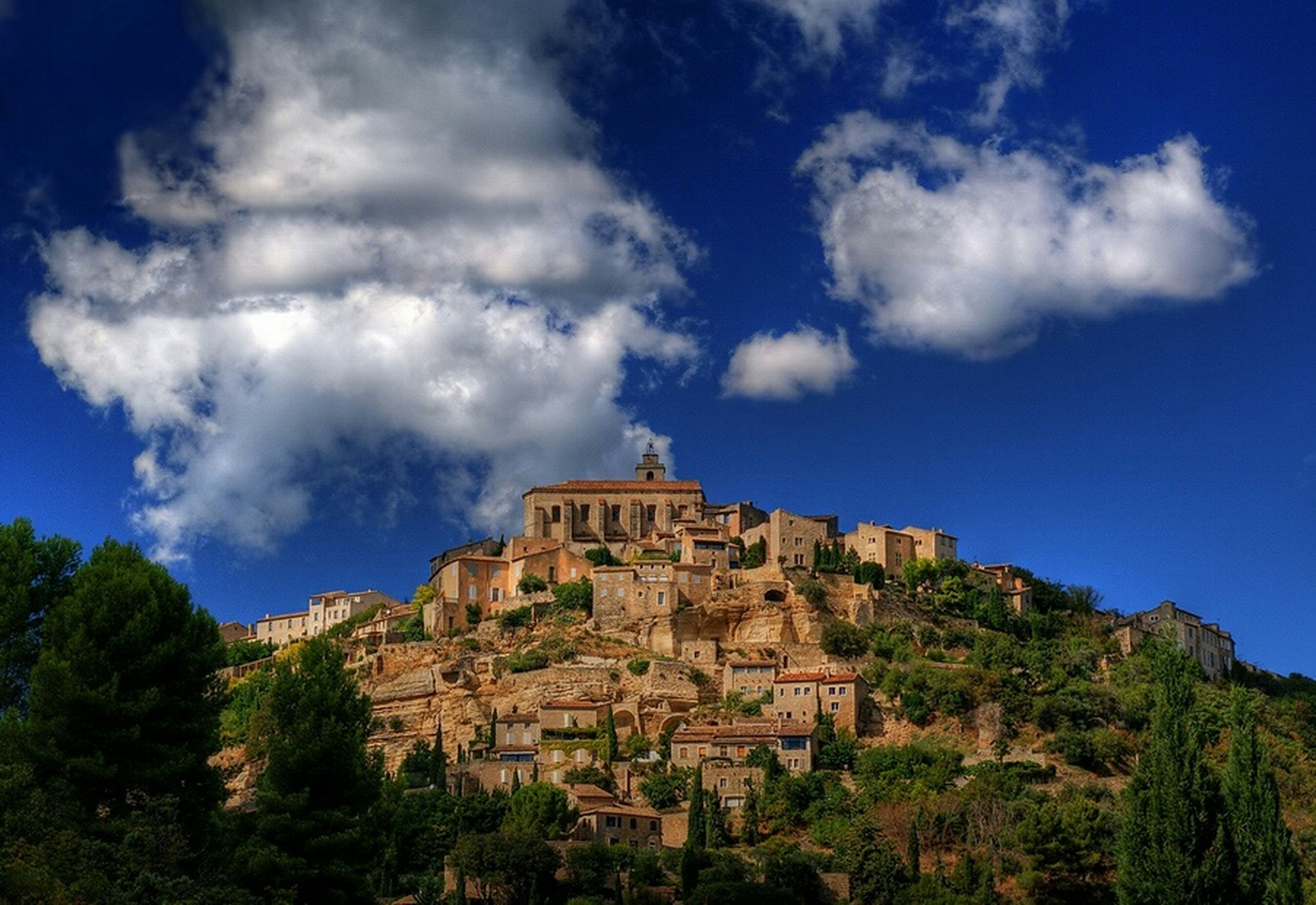 architecture, built structure, building exterior, sky, tree, history, low angle view, blue, cloud - sky, religion, place of worship, cloud, the past, spirituality, castle, old ruin, mountain, ancient, church