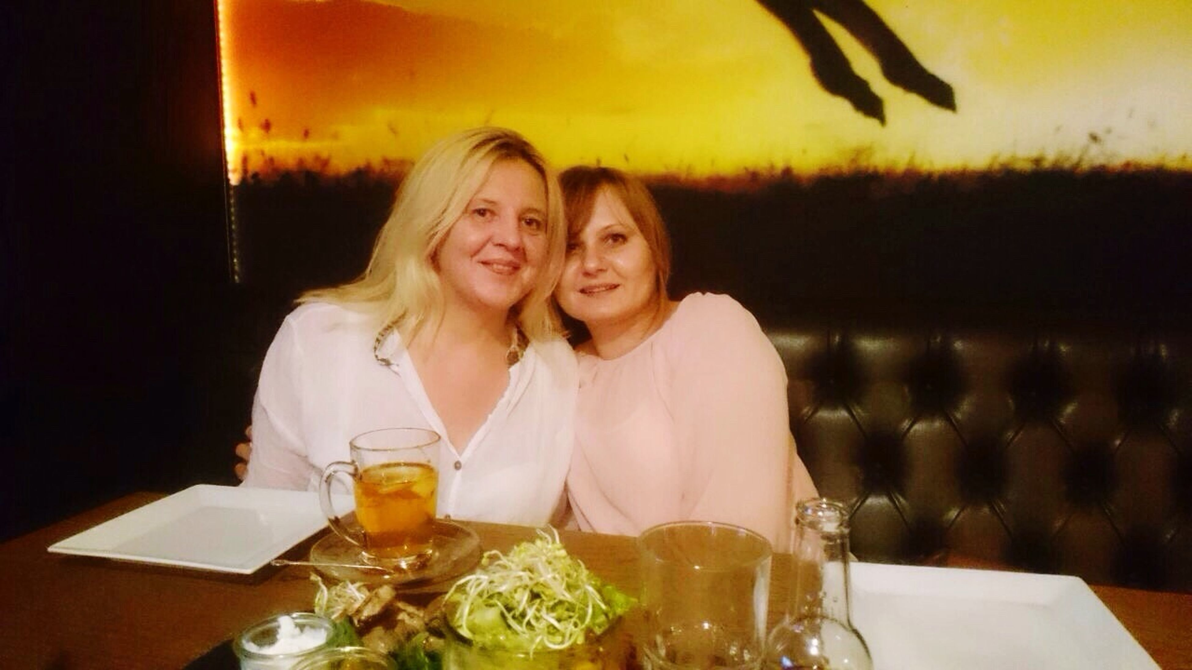 table, two people, food and drink, sitting, togetherness, smiling, looking at camera, portrait, indoors, happiness, young adult, friendship, young women, real people, night, people, food, blond hair, close-up, adult, adults only