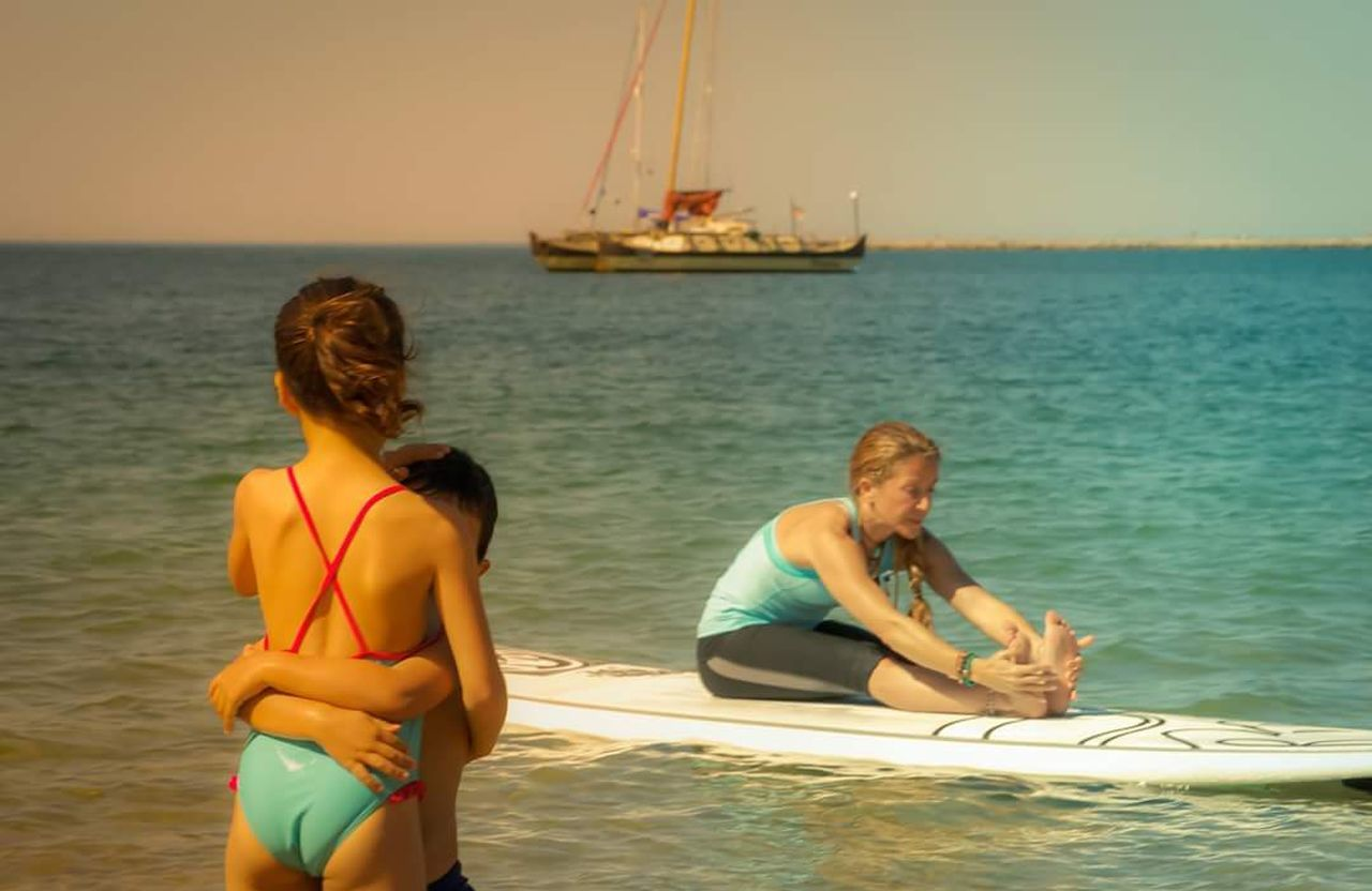 sea, water, real people, leisure activity, two people, lifestyles, sitting, vacations, nature, togetherness, nautical vessel, young women, weekend activities, beauty in nature, bikini, young adult, outdoors, beach, day, standing, full length, horizon over water, sailing, sky