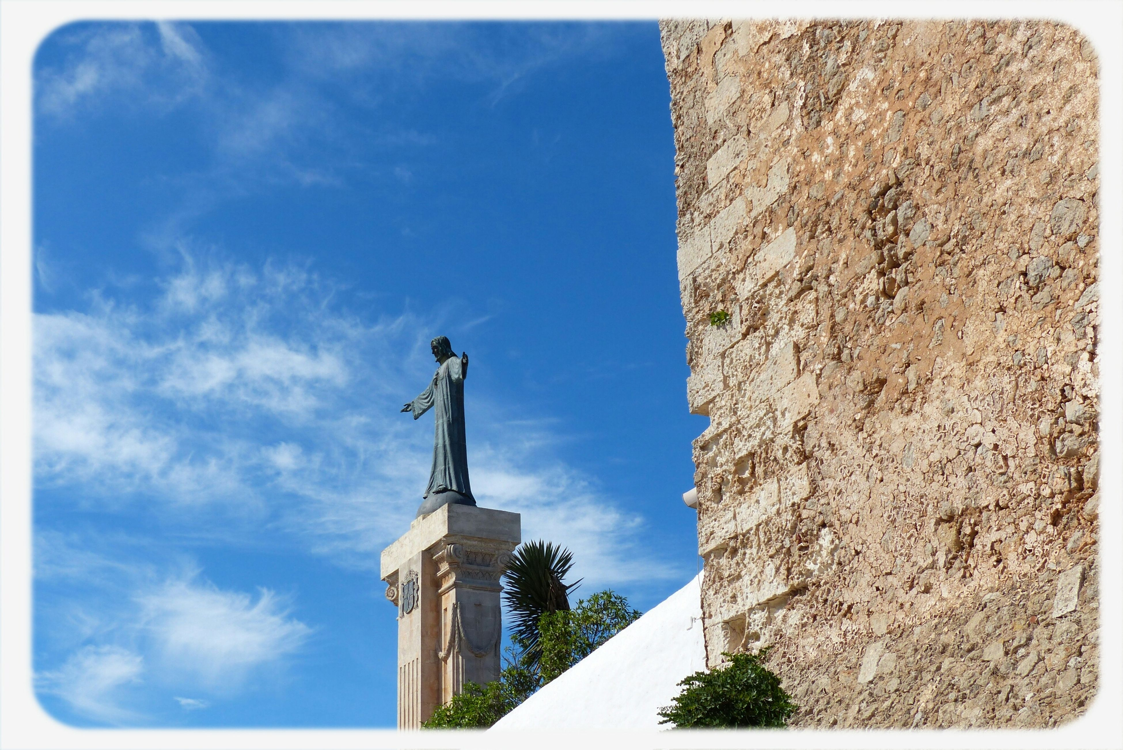 low angle view, architecture, transfer print, built structure, building exterior, sky, blue, auto post production filter, human representation, statue, history, sculpture, cloud, day, tower, cloud - sky, religion, sunlight, art and craft