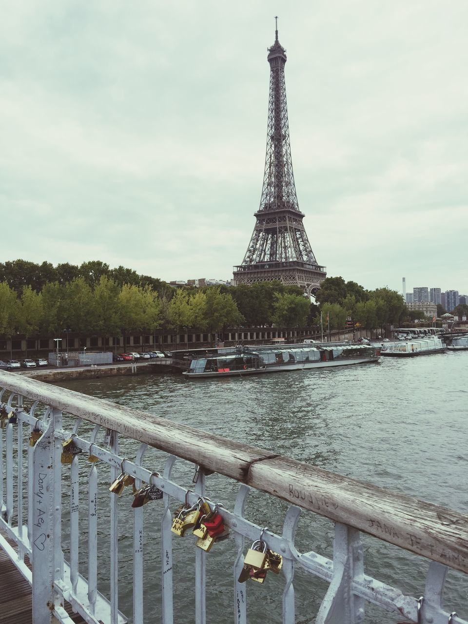 architecture, padlock, built structure, railing, travel destinations, metal, water, sky, tower, love lock, outdoors, day, river, lock, bridge - man made structure, protection, no people, building exterior, cloud - sky, city, tree, nature
