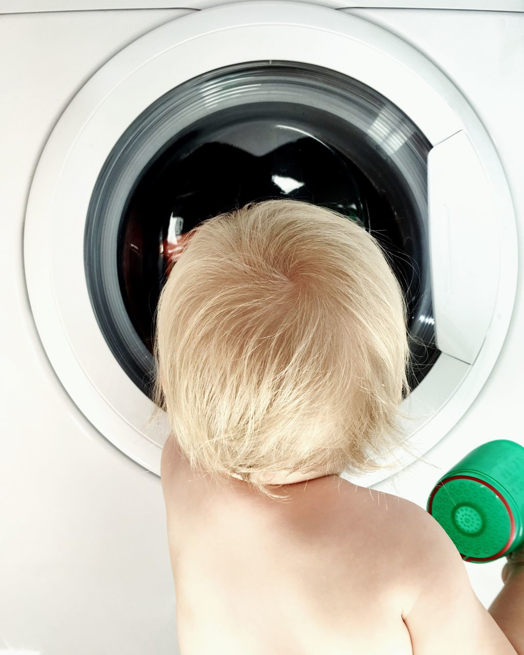 Rear View Of Boy Looking At Washing Machine