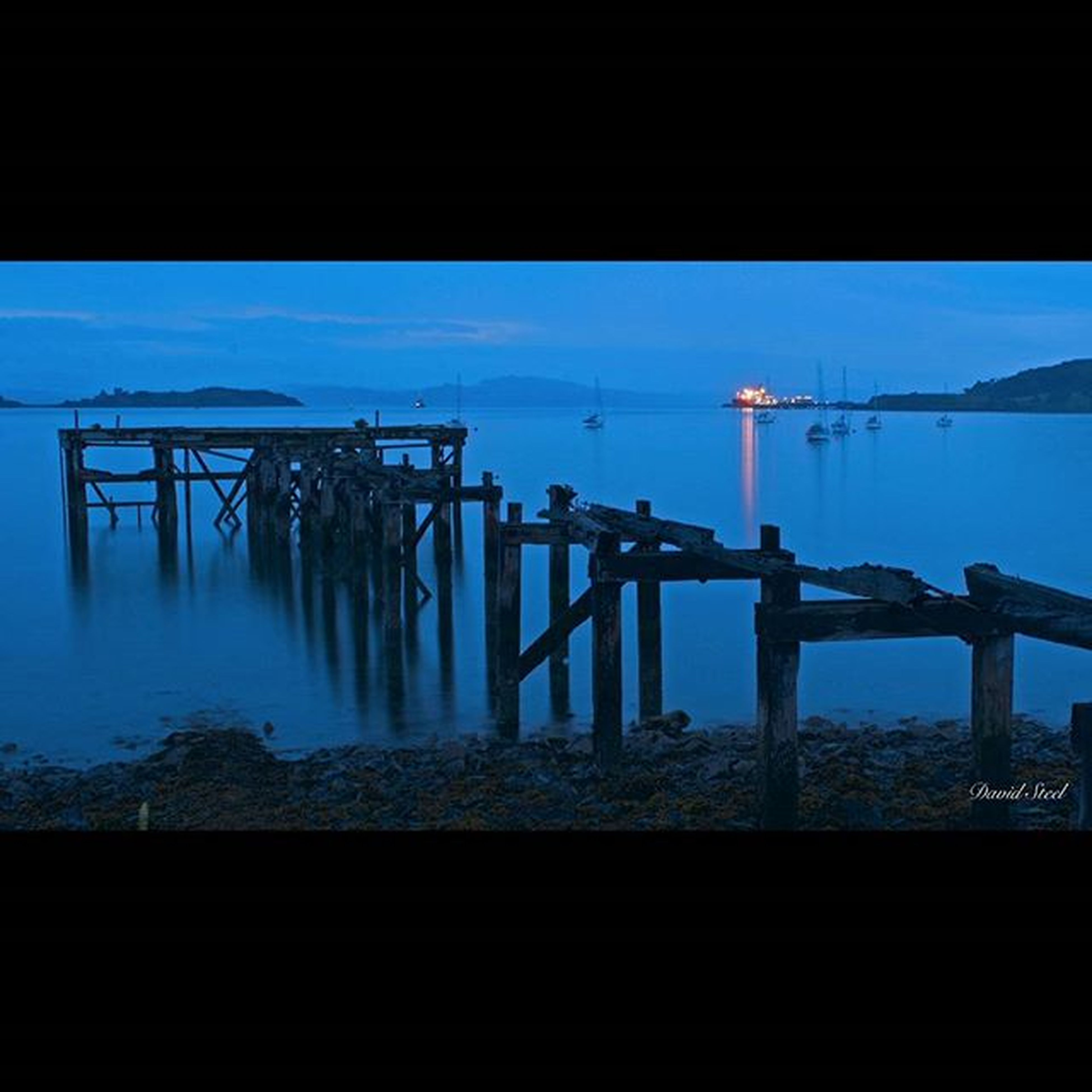 water, sea, blue, built structure, architecture, silhouette, sky, reflection, connection, bridge - man made structure, river, transportation, nature, waterfront, dusk, horizon over water, indoors, pier, tranquility