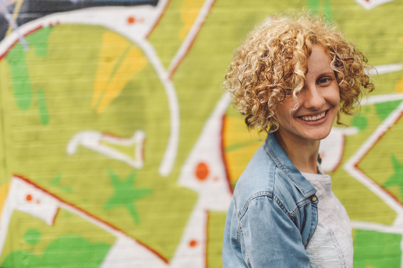 Blonde Casual Clothing Close-up Colour Of Life Confidence  Curly Hair Day Focus On Foreground Front View Girl Graffiti Graffiti Art Happiness Headshot Jacket Leisure Activity Lifestyles Outdoors Person Portrait Smiling Street Art Toothy Smile People And Places