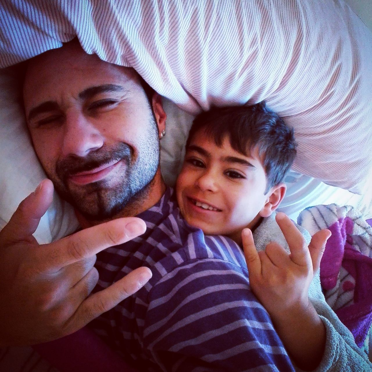Portrait Of Man With His Son Gesturing Horn Sign While Lying On Bed