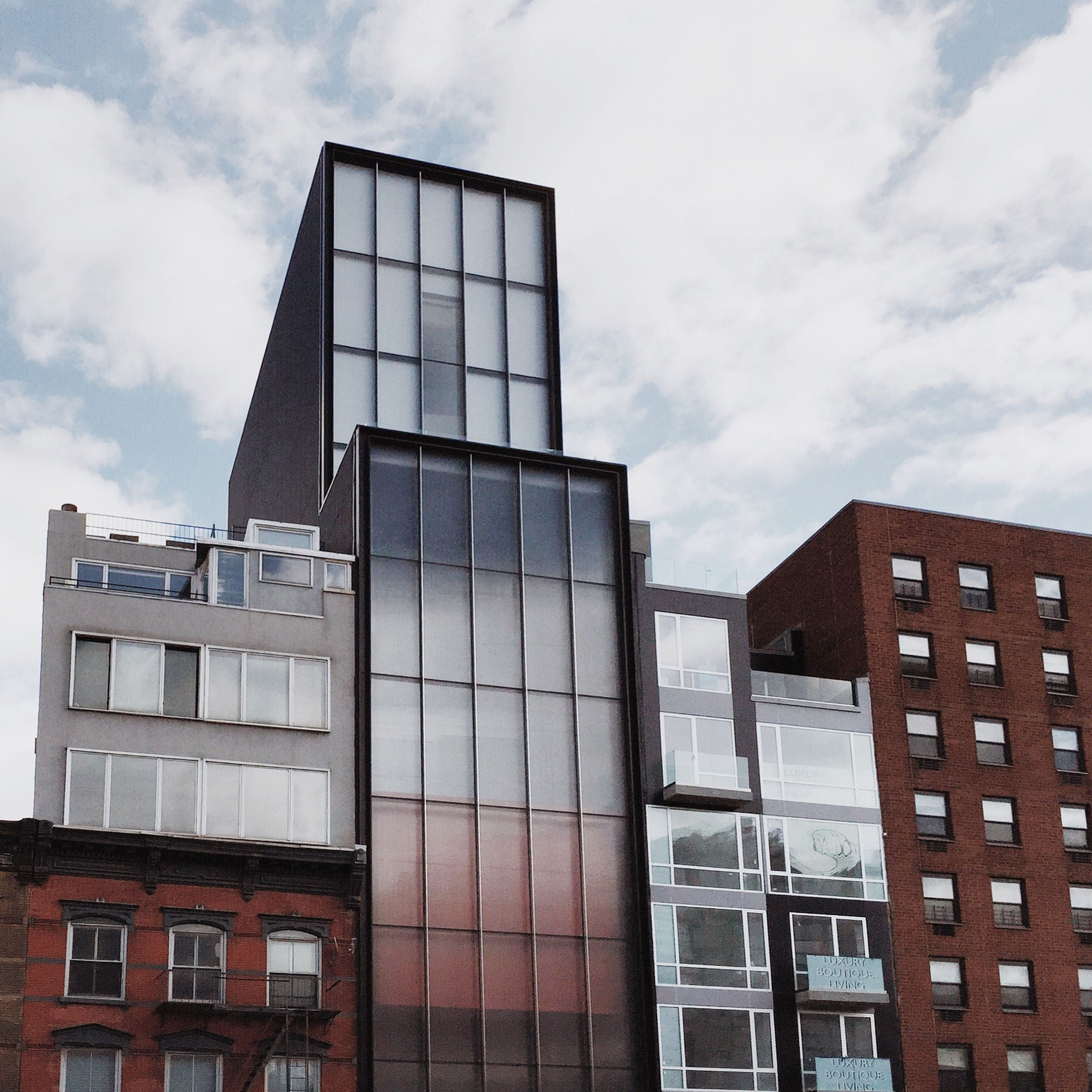 architecture, building exterior, built structure, low angle view, sky, modern, window, glass - material, building, city, office building, cloud - sky, reflection, cloud, tall - high, day, skyscraper, cloudy, outdoors, no people
