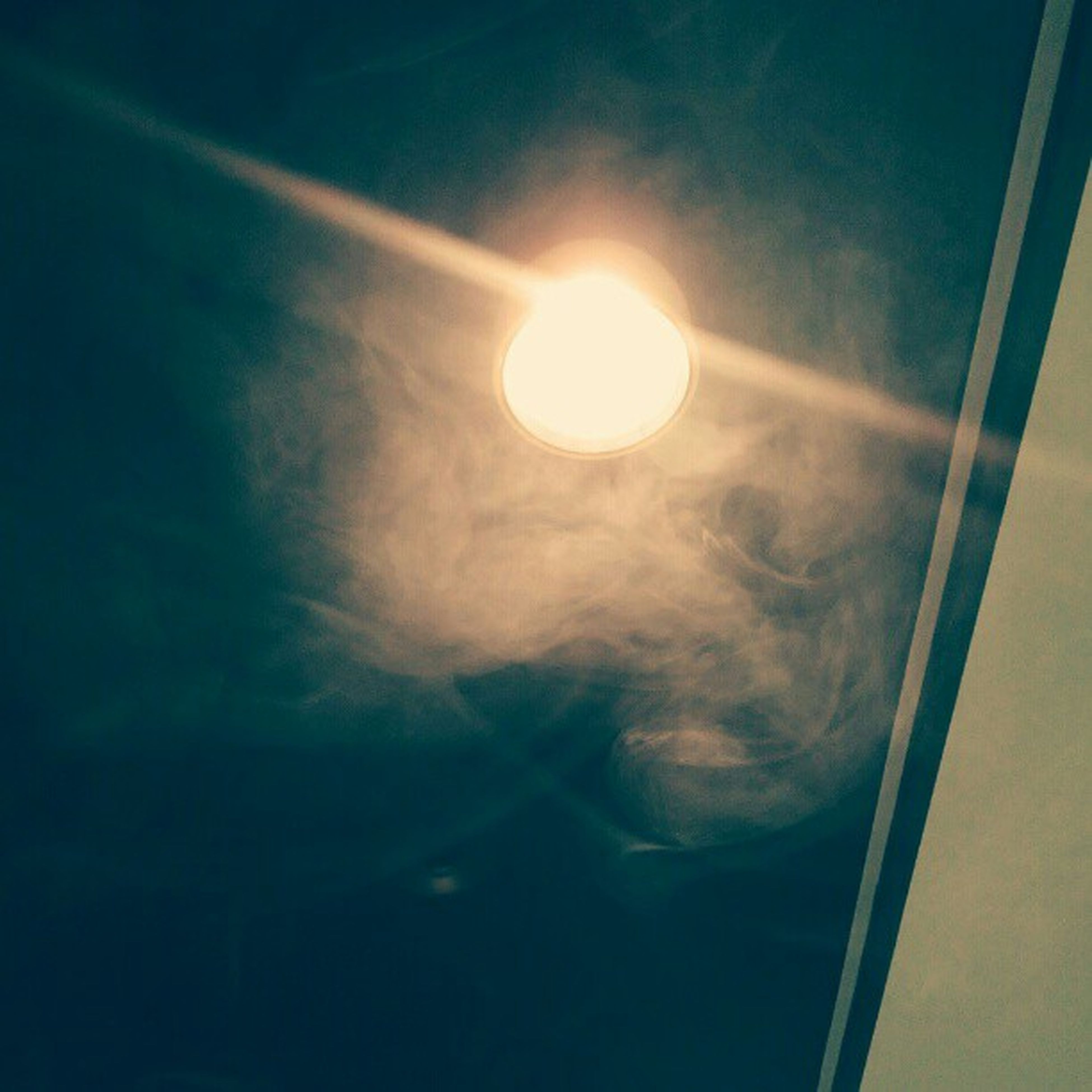 low angle view, sky, moon, window, lighting equipment, indoors, glass - material, illuminated, night, sun, cloud - sky, nature, no people, lens flare, built structure, street light, sunlight, transparent, reflection