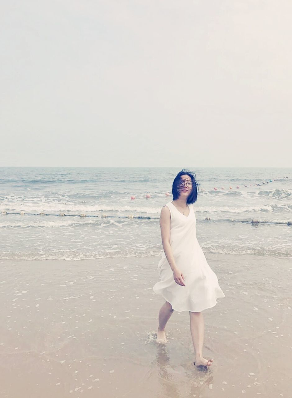 sea, beach, real people, horizon over water, standing, one person, full length, nature, lifestyles, rear view, sand, clear sky, outdoors, scenics, beauty in nature, sky, water, young adult, leisure activity, day, ankle deep in water, young women, wedding dress, bride, people