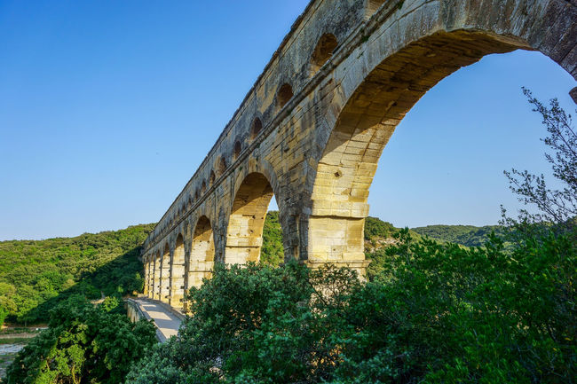 The majestic Roman aqueduct, the highest surviving - Pont du Gard. The unique architectural structure of the ancient world, entered in the UNESCO World Heritage List Ancient Architecture Ancient Civilization Antique Arch Architectural Column Architecture Blue Built Structure Clear Sky Day Green Color Growth Historical Building Historical Monuments History Landmark Nature No People Nobody Outdoors Sky Sunny Tourism Tranquility Travel Destinations
