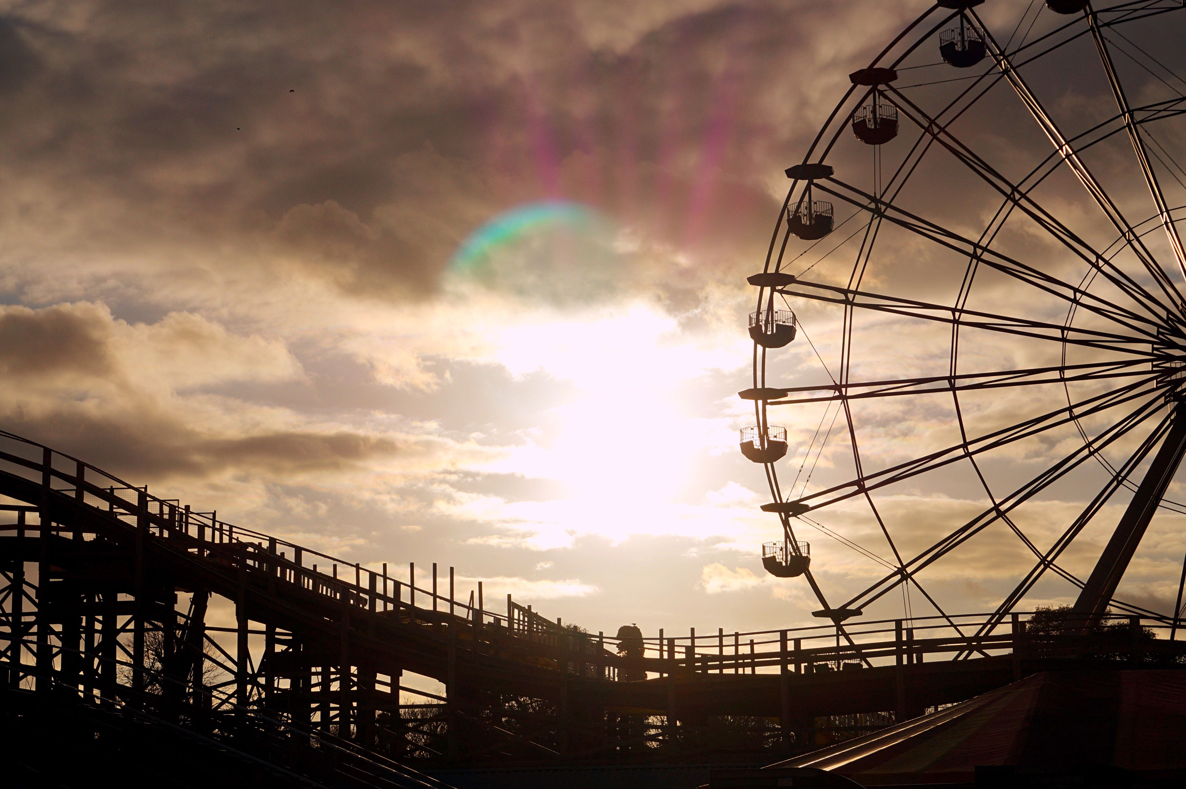 low angle view, sky, built structure, ferris wheel, cloud - sky, amusement park, cloud, amusement park ride, architecture, engineering, city, cloudy, outdoors, day, bridge, cloudscape, outline, no people, scenics, big wheel