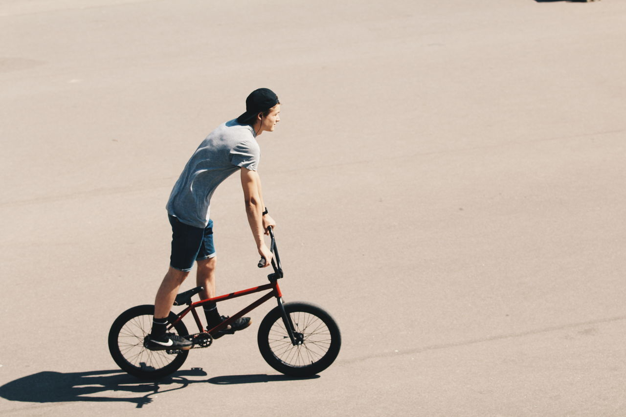 full length, bicycle, one person, cycling, riding, transportation, exercising, day, helmet, sport, young adult, outdoors, headwear, adult, people