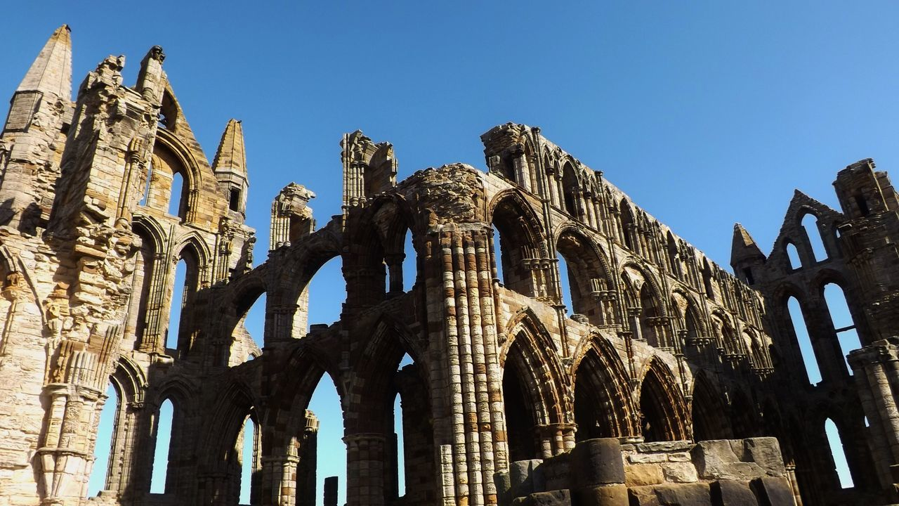 Low angle view of arched wall against clear blue sky