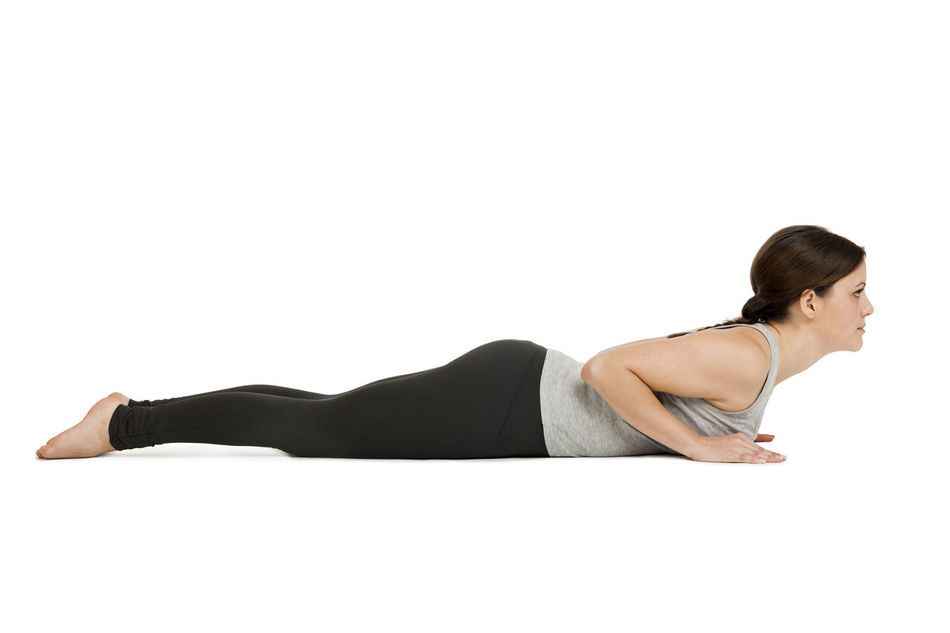 Side full body view of a young woman white background the Yoga position the Cobra (Bhujangasana) showing in the home position. Asana Beautiful Woman Beauty Bhujangasana Copy Space Cut Out Day Flexibility Full Length Indoors  Lifestyles Lying On The Belly One Person People Profile View Side View Studio Shoot Studio Shot White Background Yog Postion Yoga Young Adult Young Women