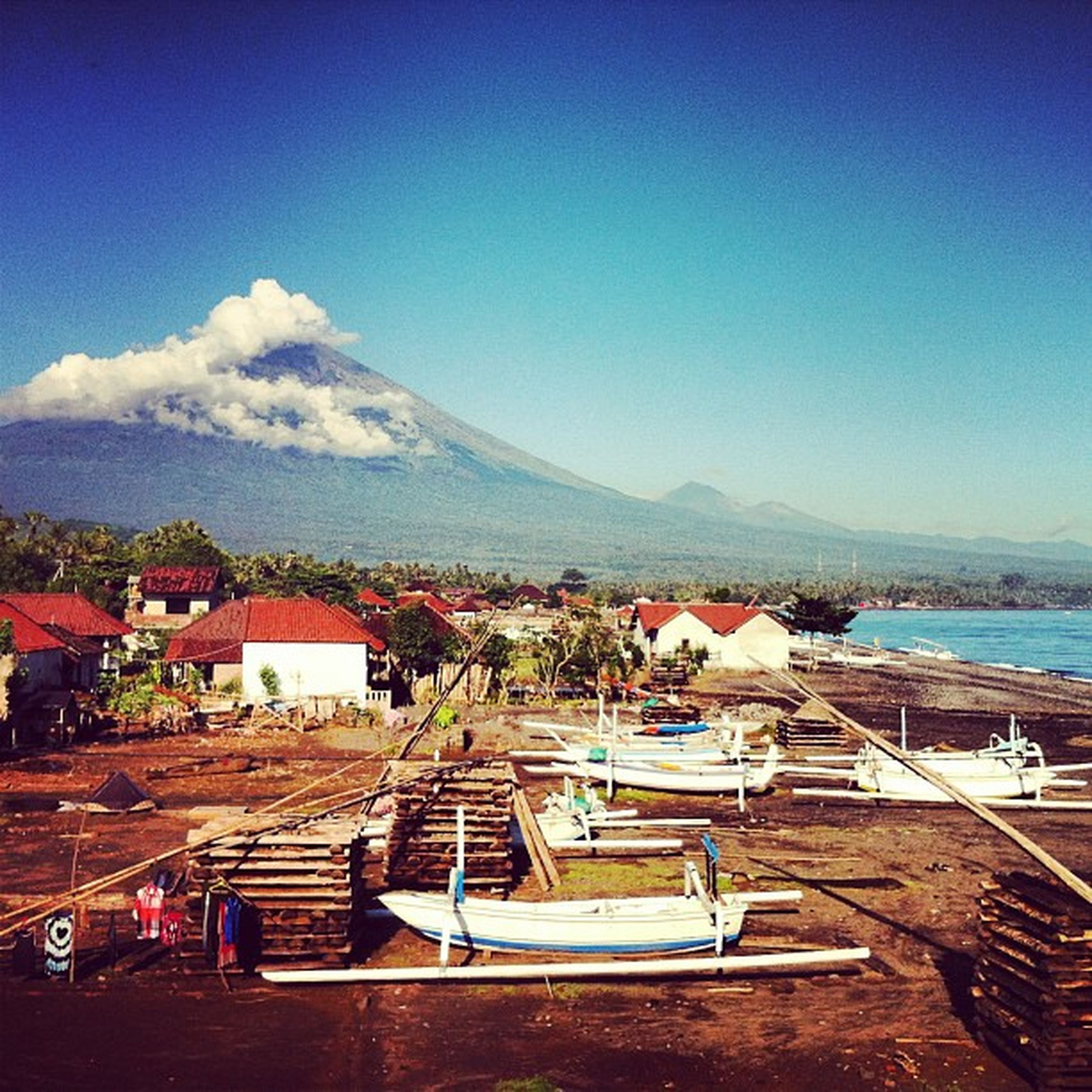 The view from my balcony: blacksand beach & fishing village of Amed w/ Mt. Agung in the background Bali INDONESIA