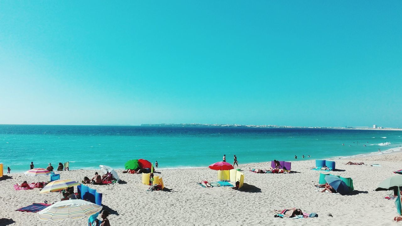 beach, sea, sand, horizon over water, shore, water, vacations, copy space, summer, clear sky, nature, outdoors, day, weekend activities, beauty in nature, blue, tranquility, scenics, leisure activity, large group of people, real people, men, sky, people