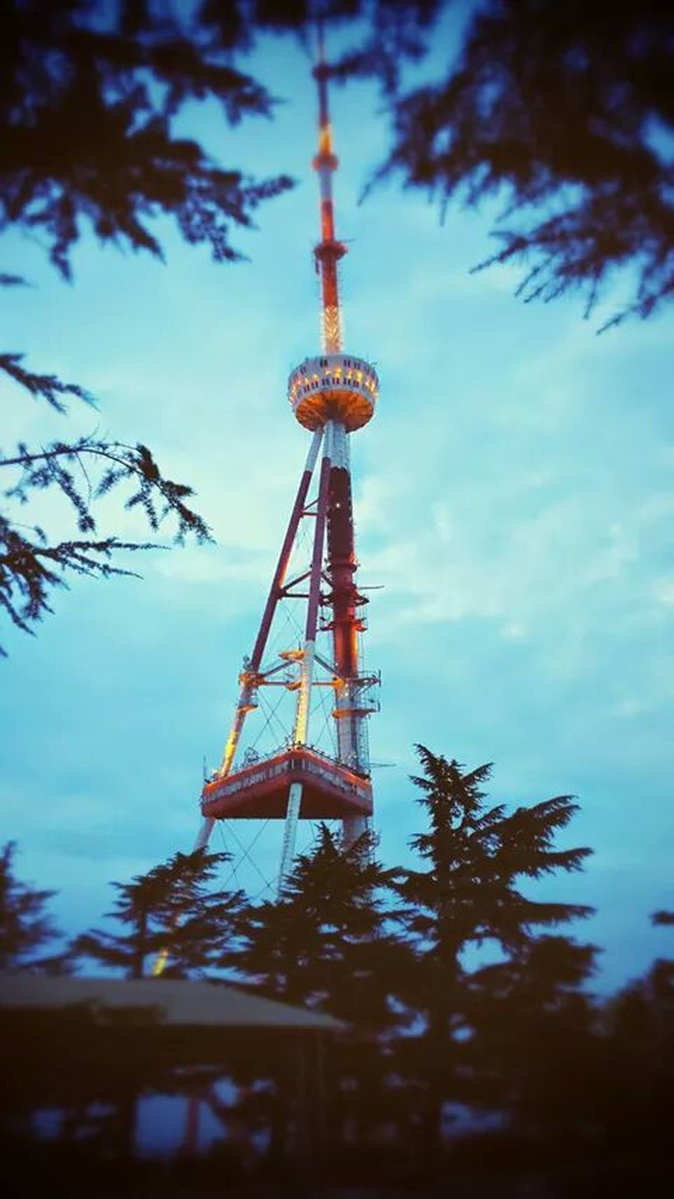 tower, tall - high, communications tower, tree, sky, low angle view, famous place, tourism, travel destinations, international landmark, built structure, architecture, capital cities, travel, communication, spire, sphere, fernsehturm, eiffel tower, dusk