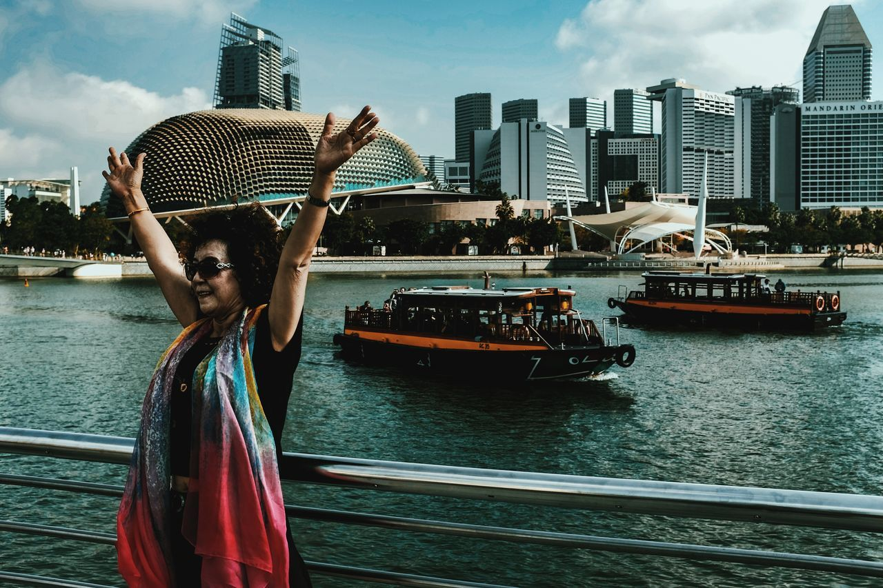 City Nautical Vessel Mode Of Transport Transportation Water Outdoors Building Exterior Sailing Leisure Activity One Person Urban Skyline Architecture Sky Cityscape Woman Tourist Esplanade Singapore Sea River Taxi Street Photography Streetphotography Streetphoto_color Everybodystreet FUJIFILM X100S The City Light