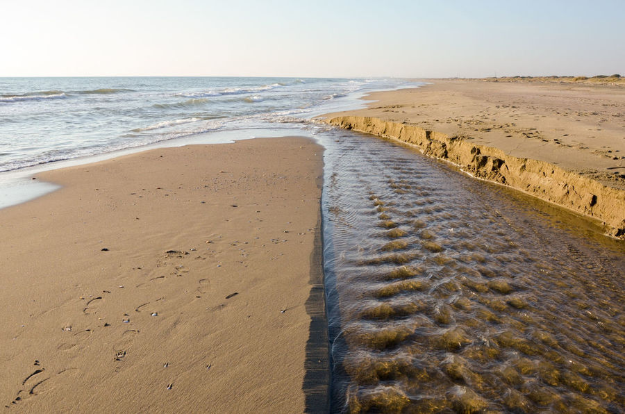 Water flows to the sea between sand dunes Beach Sea Sand Horizon Over Water Nature Wave No People Outdoors Day Water Flow Winter Landscape Natural Beauty Sunset Reflections Scenic View