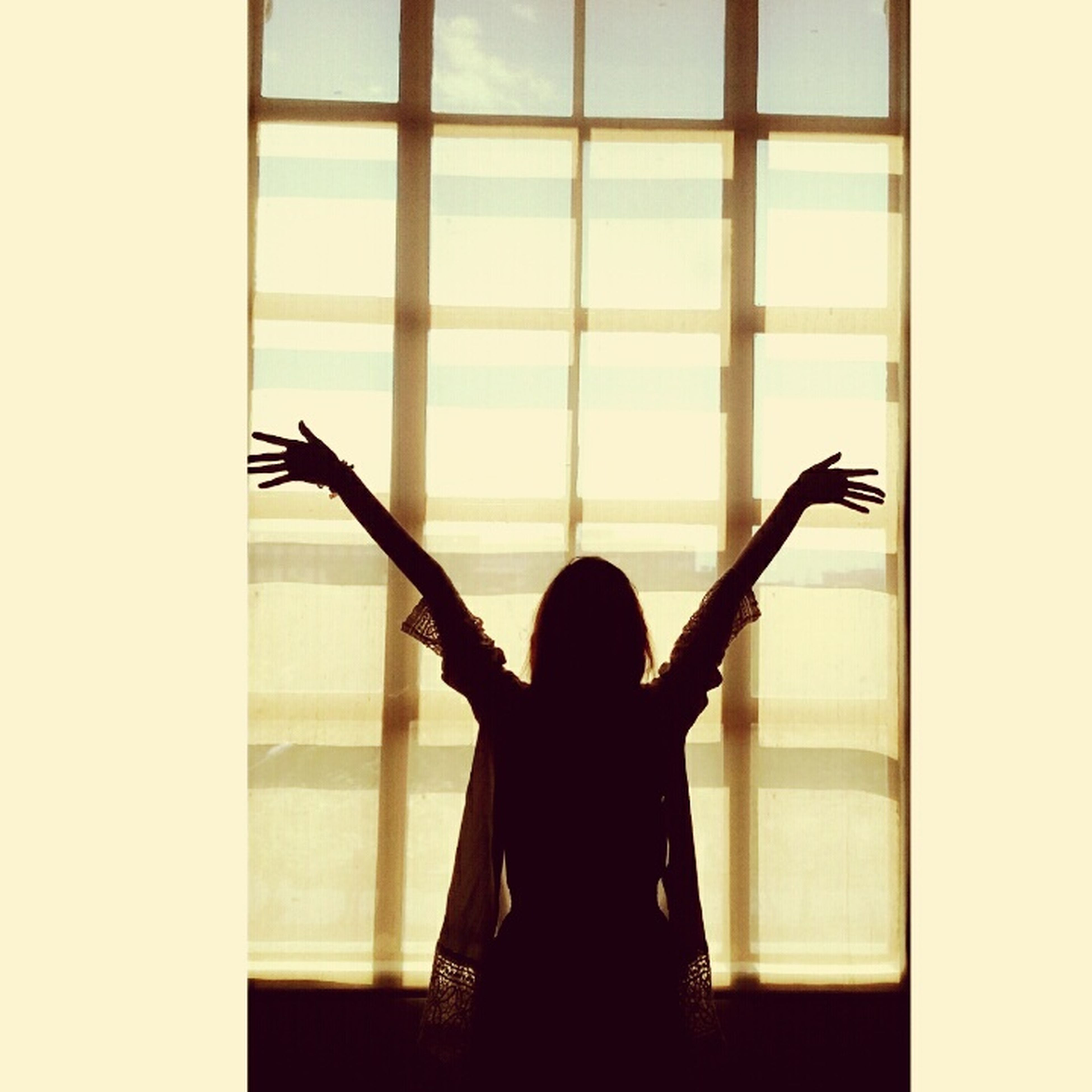 indoors, lifestyles, window, standing, leisure activity, glass - material, person, three quarter length, silhouette, holding, transparent, young adult, rear view, young women, side view, wireless technology, full length, photographing