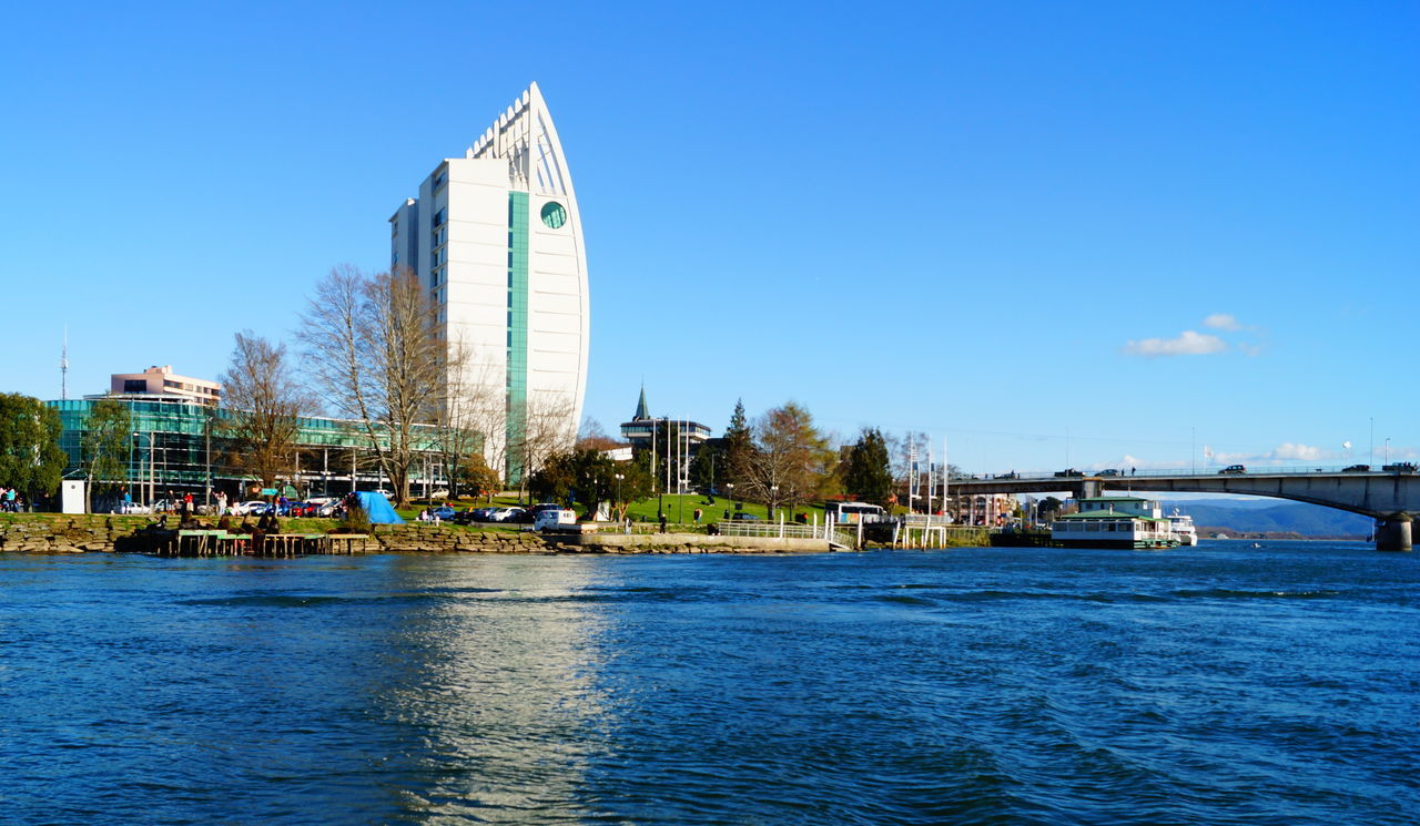 architecture, built structure, building exterior, blue, clear sky, day, water, outdoors, transportation, waterfront, sky, nautical vessel, no people, city, travel destinations, skyscraper, nature, tree