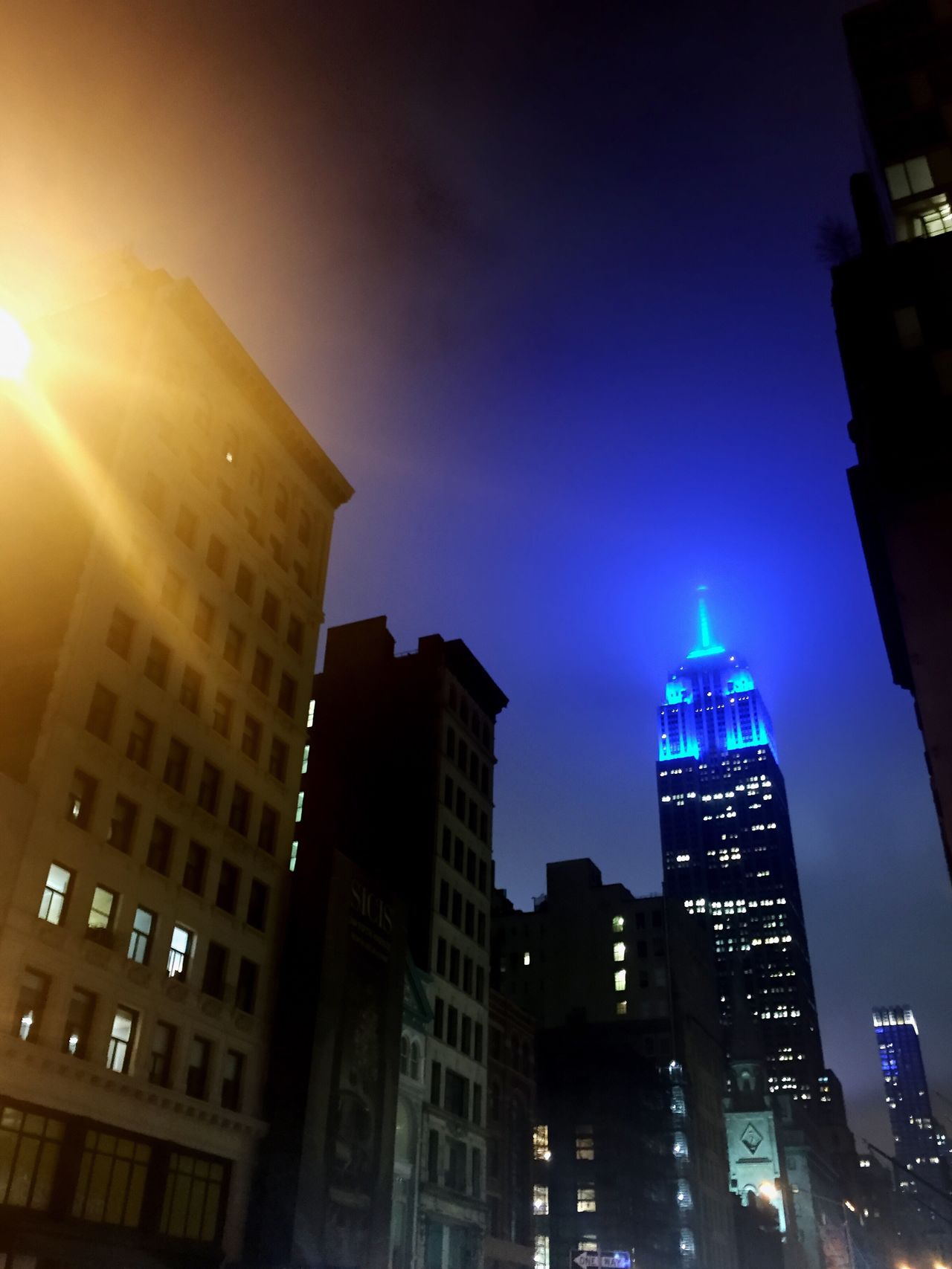 Empire State Building lit up at night. Building Exterior City Illuminated Skyscraper Night Sky Outdoors Cityscape Downtown District Low Angle View Architecture No People Blue Lighting Yellow Lighting Blue Yellow Street Built Structure Urban Glow Glowing Fog Downtown Calm Darkness