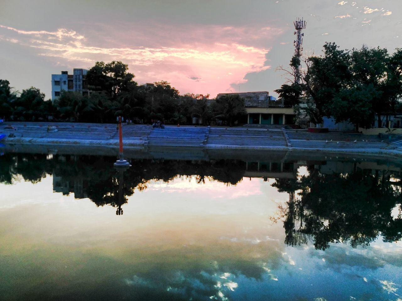 reflection, water, architecture, tree, sky, built structure, sunset, building exterior, waterfront, cloud - sky, outdoors, lake, no people, nature, puddle, day, beauty in nature, city
