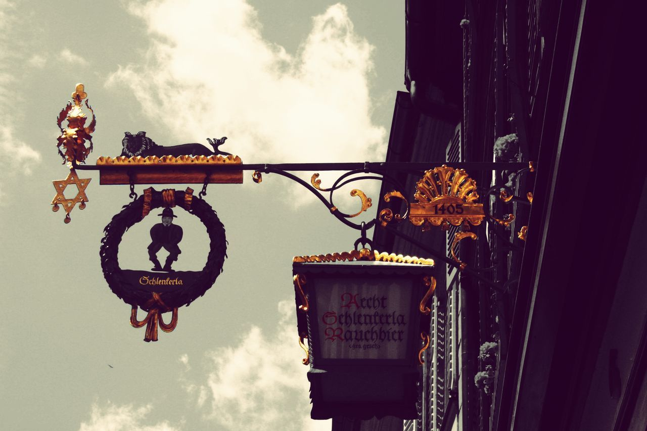 hanging, text, communication, day, sky, no people, outdoors, cloud - sky, low angle view, spirituality, close-up, architecture