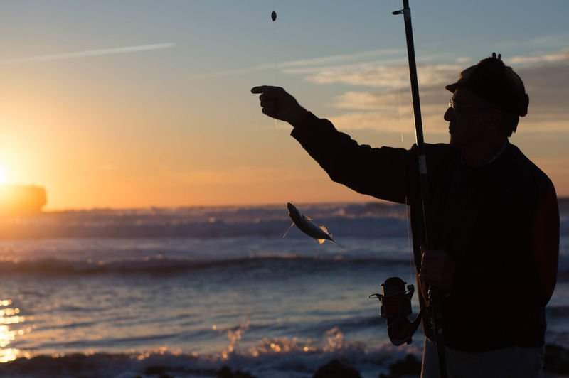 Silhouette One Person Beach Sunset Sea Adults Only Adult One Man Only People Only Men Leisure Activity Sky Outdoors Standing Sand Day Real People Water Nature Men Fish Fishing Fiaherman Catch Relax fishing rod