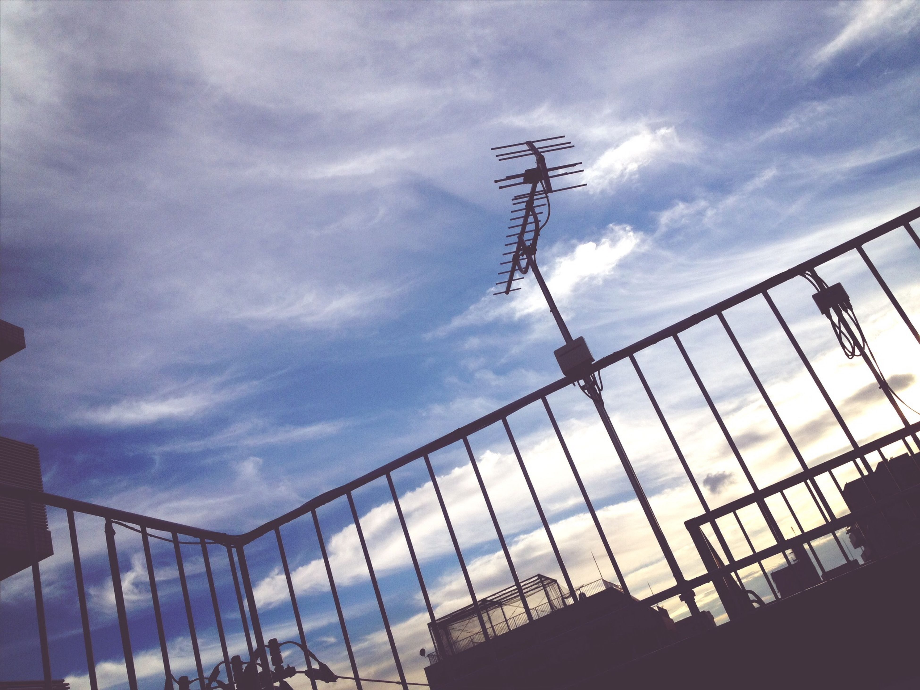 sky, cloud - sky, low angle view, cloudy, built structure, cloud, power line, cable, architecture, connection, day, fence, electricity, weather, outdoors, power supply, electricity pylon, no people, nature, railing