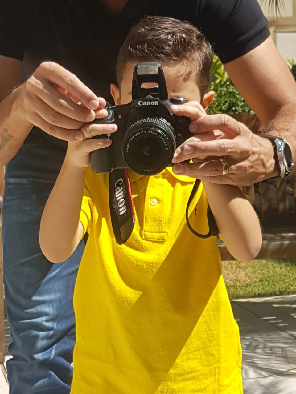 camera - photographic equipment, photography themes, photographing, technology, photographer, real people, leisure activity, digital camera, holding, yellow, one person, professional occupation, digital single-lens reflex camera, slr camera, camera, day, lifestyles, outdoors, men, close-up, human hand