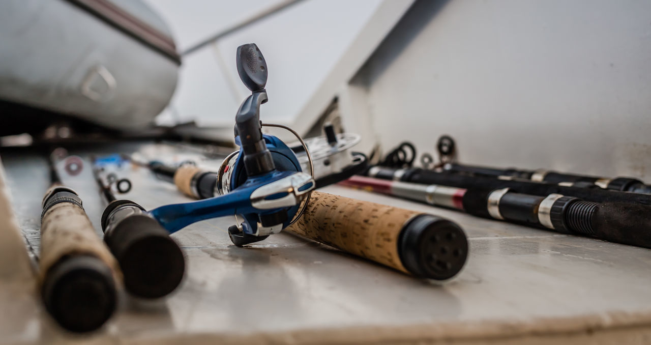 Close-Up Of Various Fishing Rods On Table