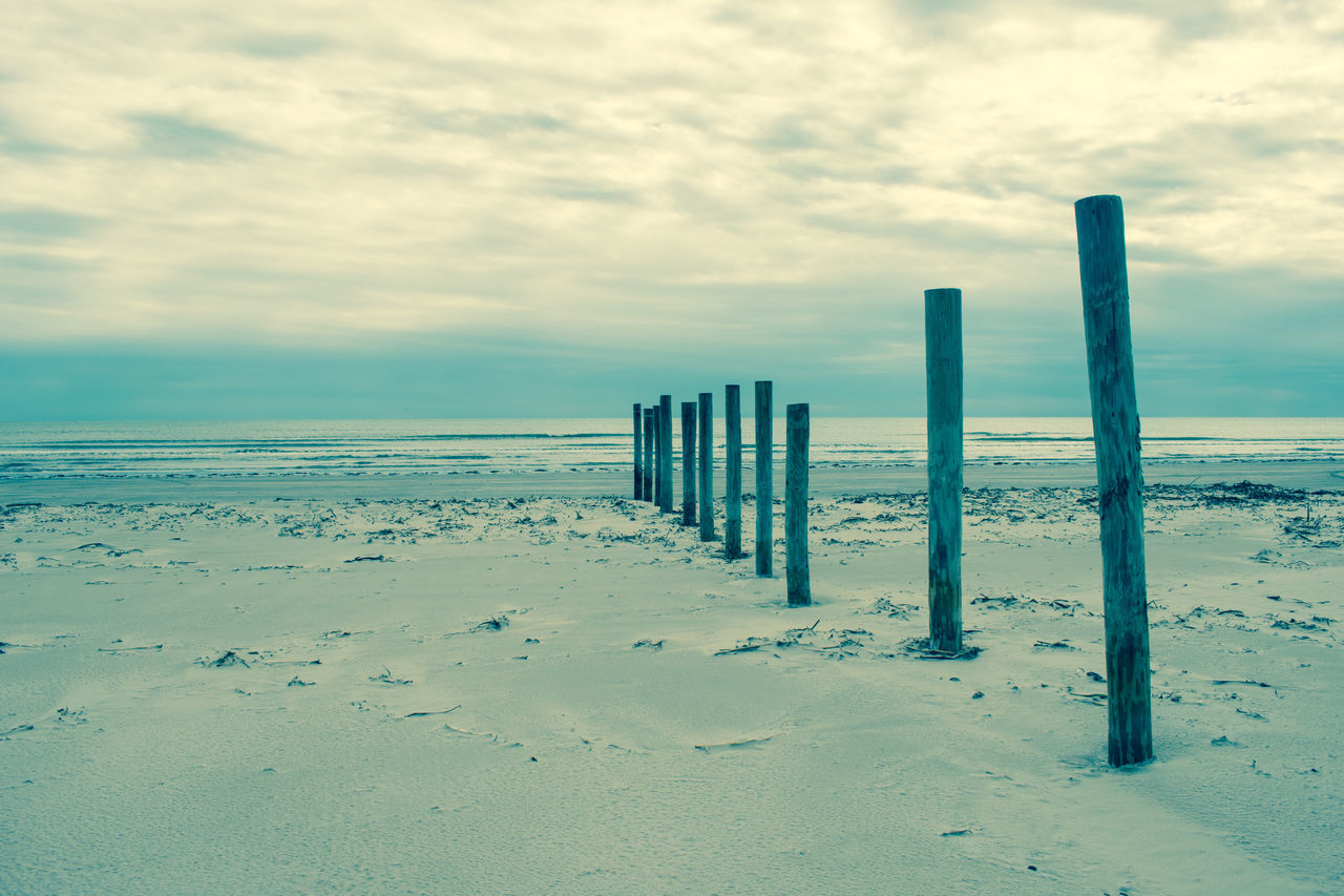 sand, sky, beach, cloud - sky, outdoors, wooden post, nature, day, no people, sea, tranquility, beauty in nature, landscape, scenics, horizon over water