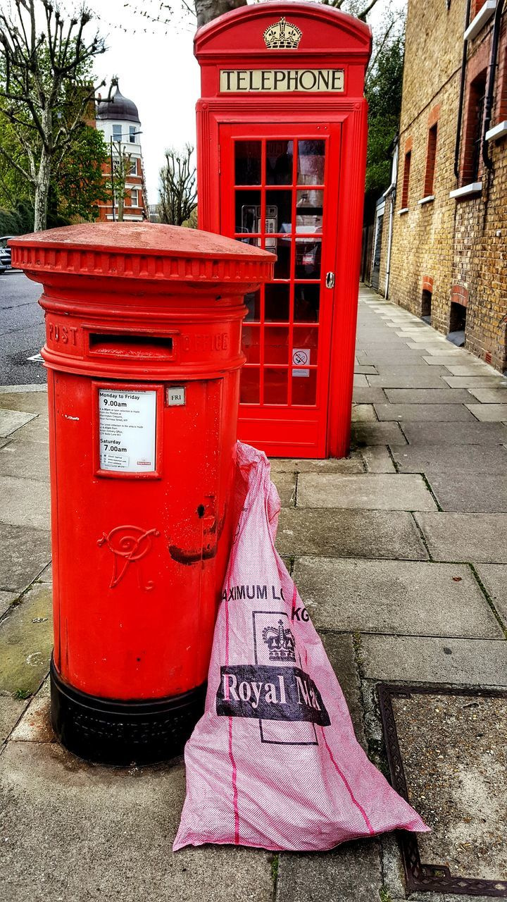 communication, red, western script, text, public mailbox, mail, correspondence, day, outdoors, architecture, building exterior, convenience, built structure, telephone booth, no people, pay phone, tree, city