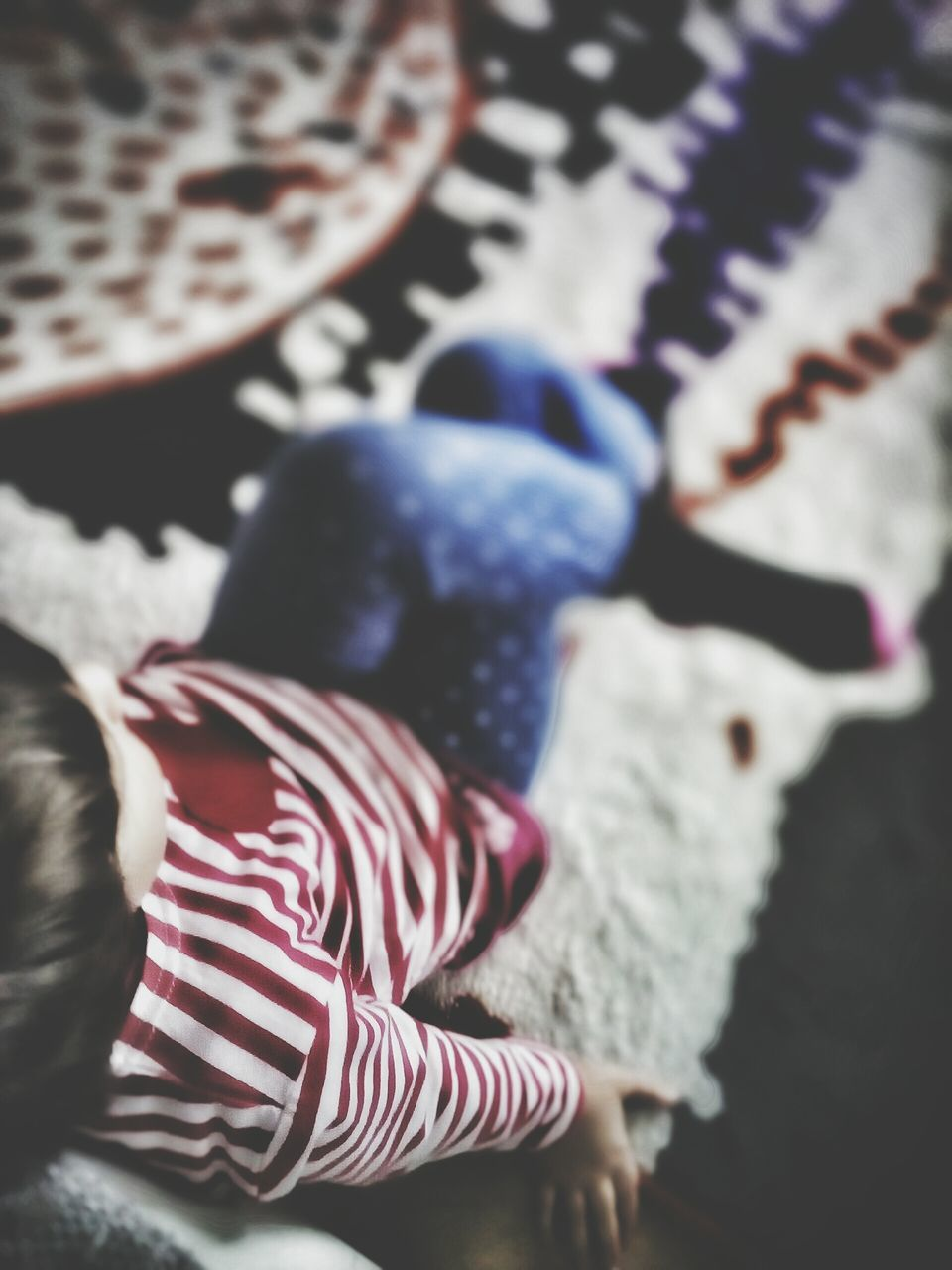 High Angle View Of Girl Sitting On Carpet At Home