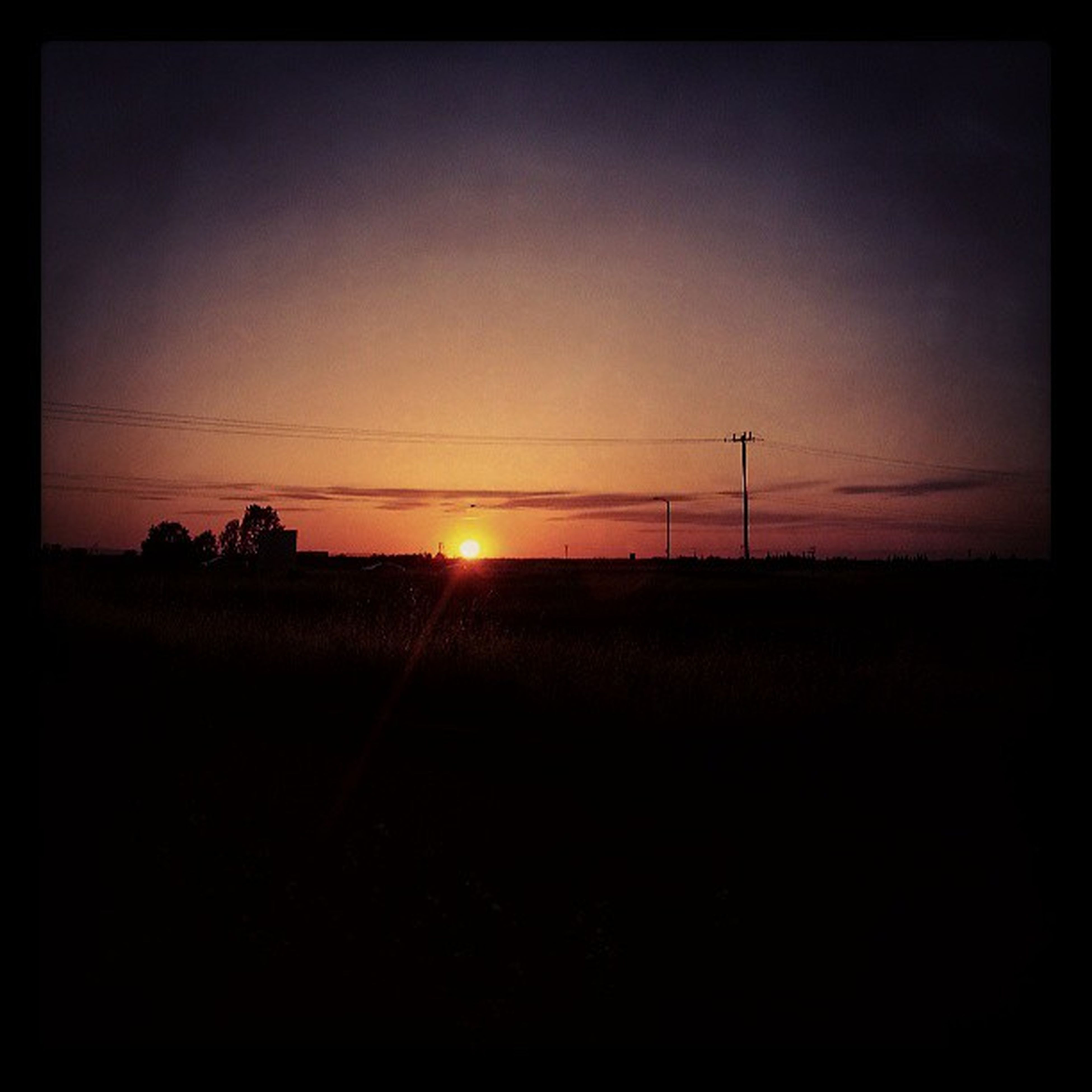 sunset, tranquil scene, sun, tranquility, silhouette, landscape, scenics, field, beauty in nature, sky, electricity pylon, nature, power line, transfer print, orange color, auto post production filter, rural scene, idyllic, sunlight, outdoors