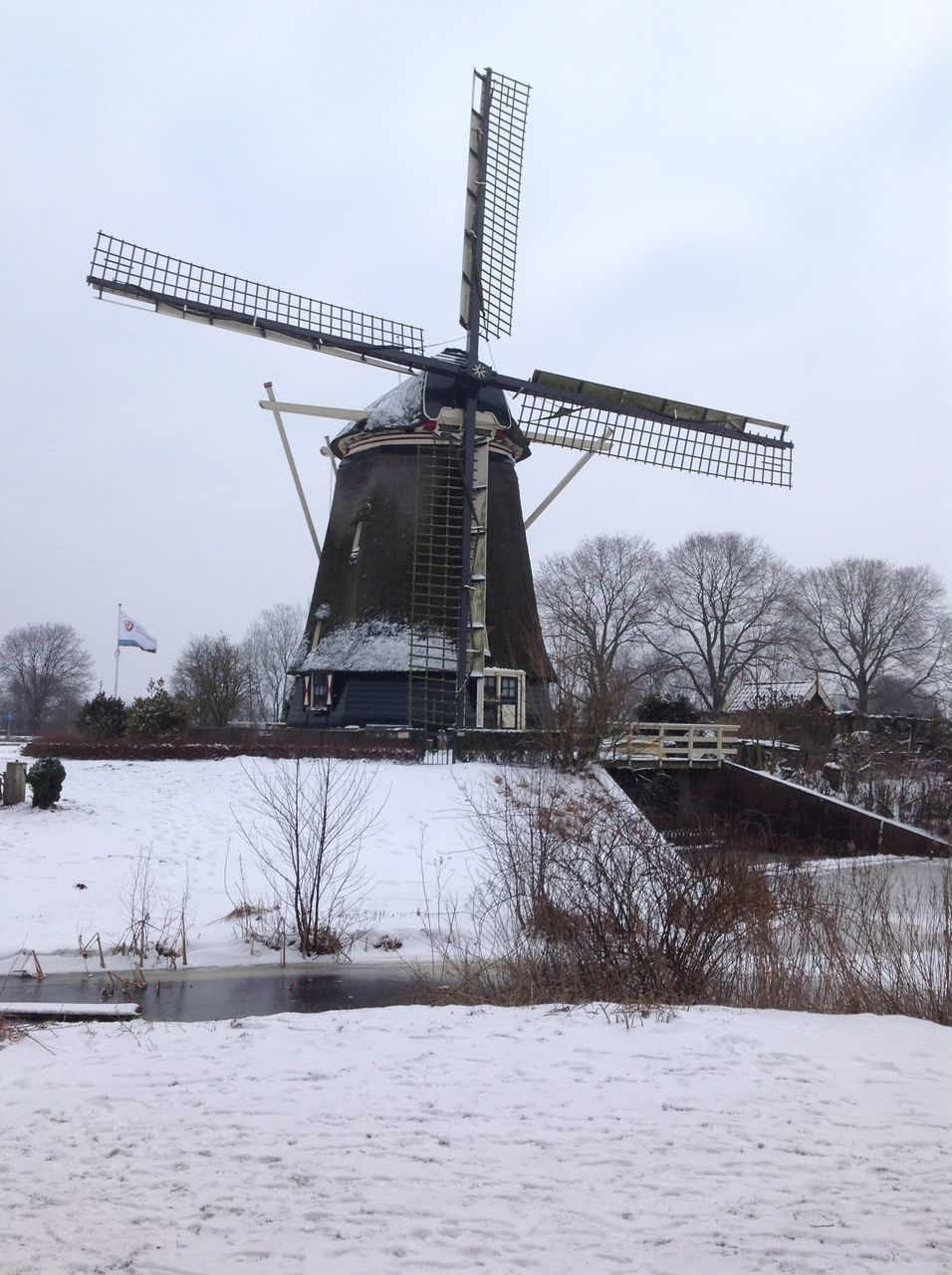 alternative energy, wind power, windmill, renewable energy, environmental conservation, wind turbine, fuel and power generation, traditional windmill, industrial windmill, cold temperature, weather, winter, snow, technology, nature, built structure, field, architecture, outdoors, day, no people, rural scene, bare tree, lake, sky, water, beauty in nature, tree