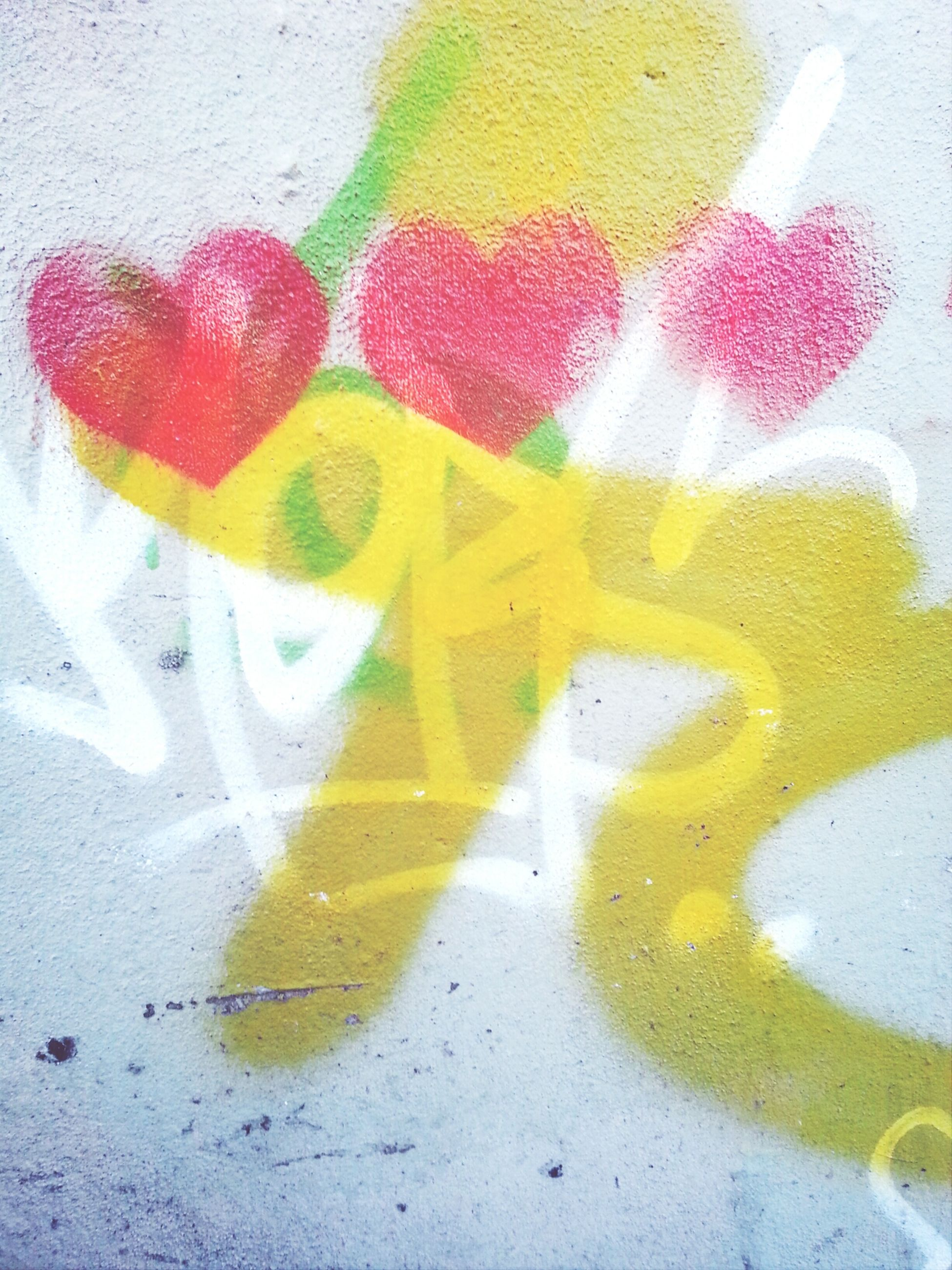 creativity, art, art and craft, close-up, human representation, wall - building feature, yellow, heart shape, high angle view, paint, graffiti, love, communication, animal representation, multi colored, anthropomorphic face, text, drawing - art product, ideas, indoors