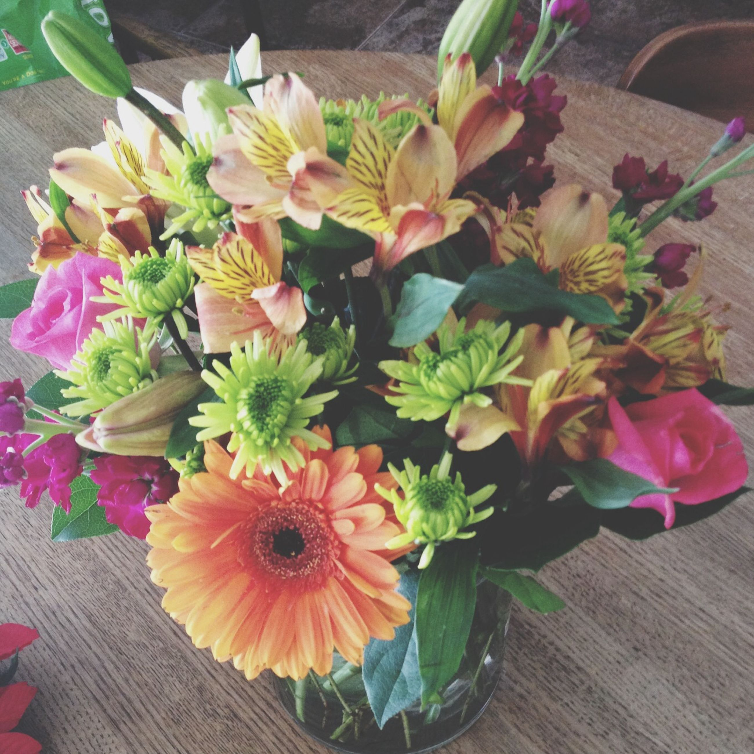 flower, freshness, petal, indoors, fragility, table, vase, flower head, high angle view, beauty in nature, bouquet, flower arrangement, plant, potted plant, nature, growth, wood - material, leaf, flower pot, bunch of flowers