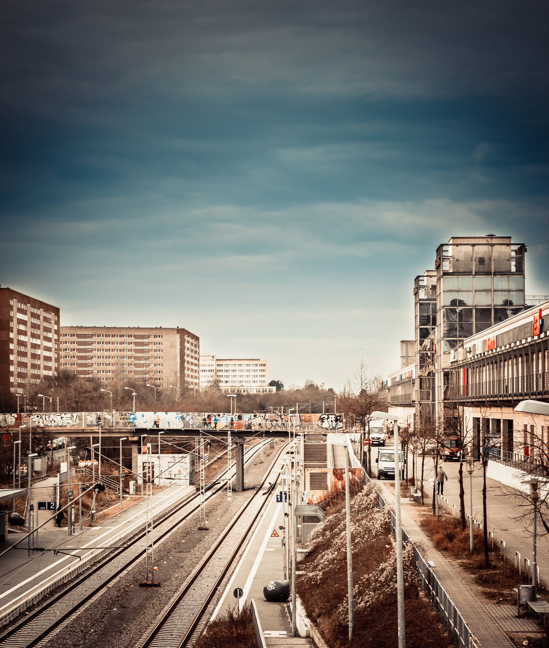 railroad track, transportation, rail transportation, built structure, sky, architecture, railway track, public transportation, building exterior, train - vehicle, cloud - sky, shunting yard, no people, outdoors, city, day