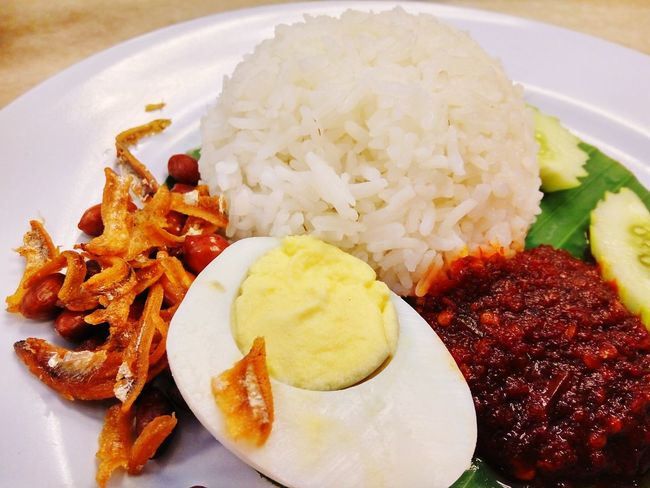 Nasi Lemak, the Malaysian cuisine Food Plate Ready-to-eat Freshness Close-up Served On Plate Cucumber Rice Eat Cuisine Hot Chili  Spicy Anchovies Egg Nasi Lemak For Breakfast Healthy Eating Local Food Tasty Malaysian