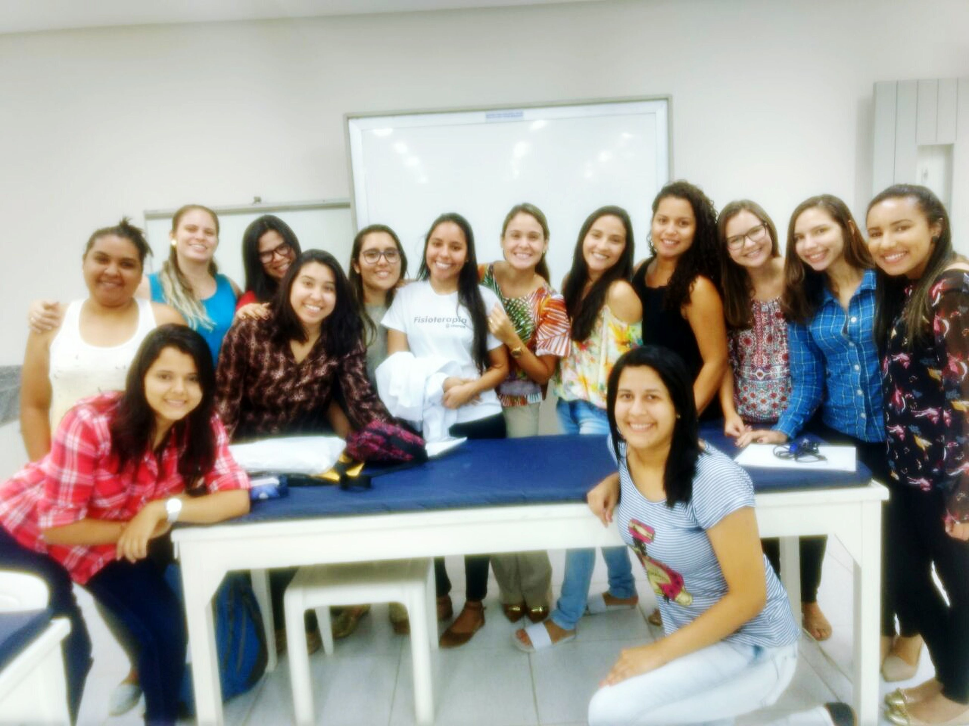 looking at camera, smiling, portrait, happiness, classroom, medium group of people, indoors, desk, sitting, student, cheerful, learning, education, real people, friendship, day, young adult, young women, adult, people